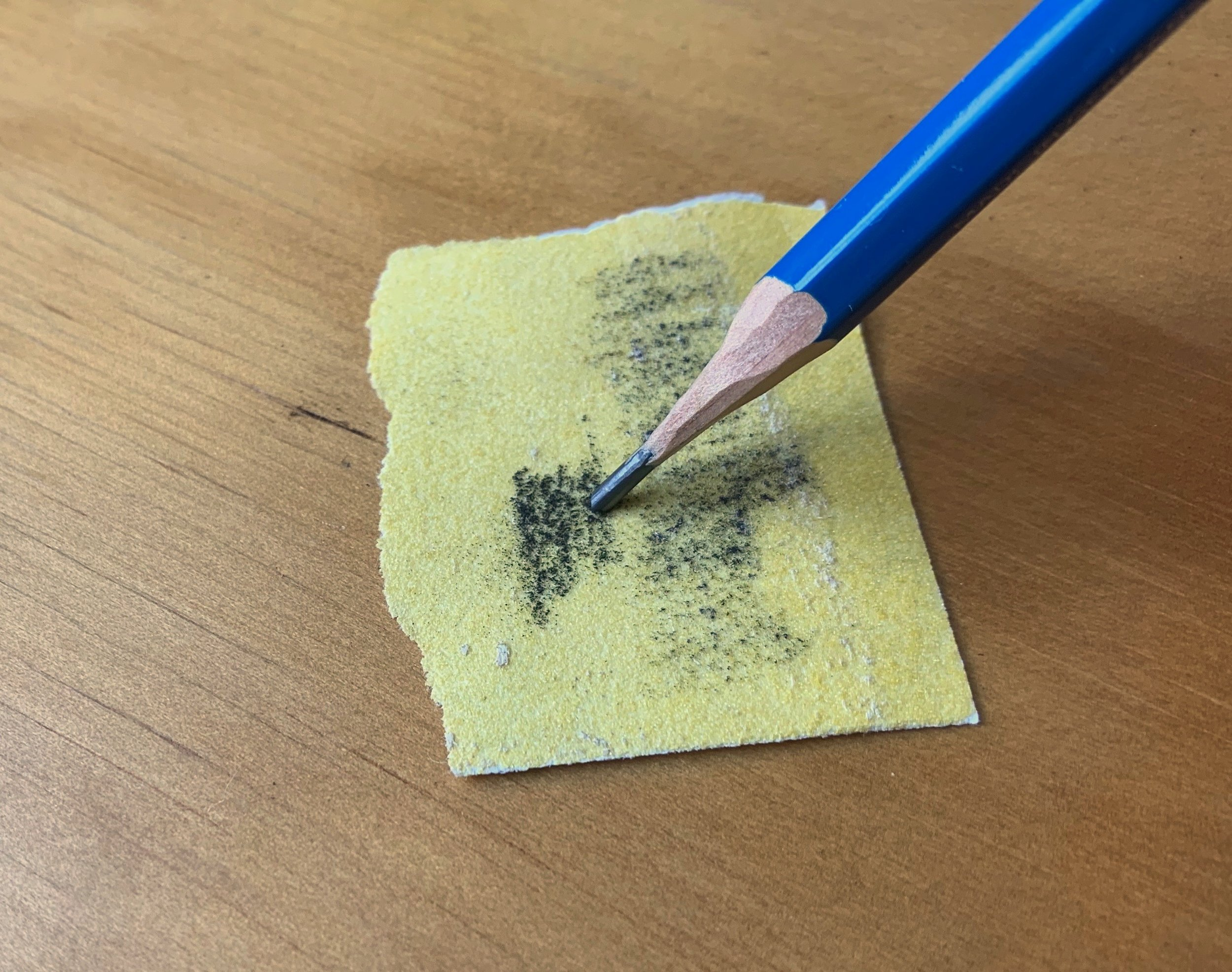 The lead of the pencil is filed on sandpaper to form a flat wedge