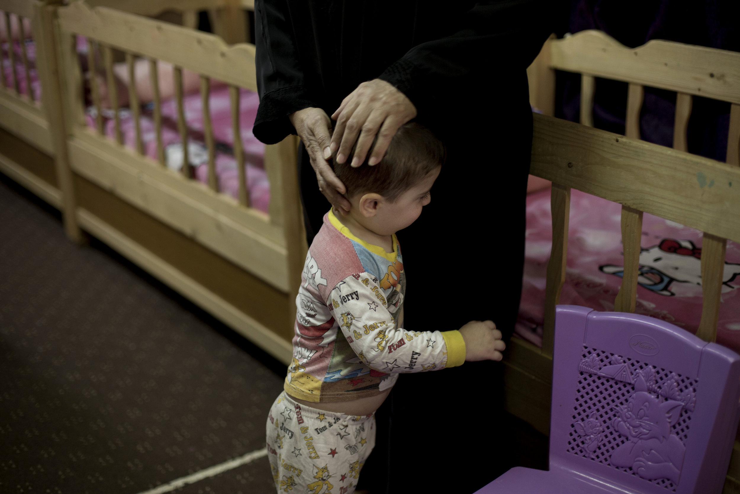 A toddler is comforted at Salhiya orphanage in Baghdad. (AP Photo/Maya Alleruzzo)