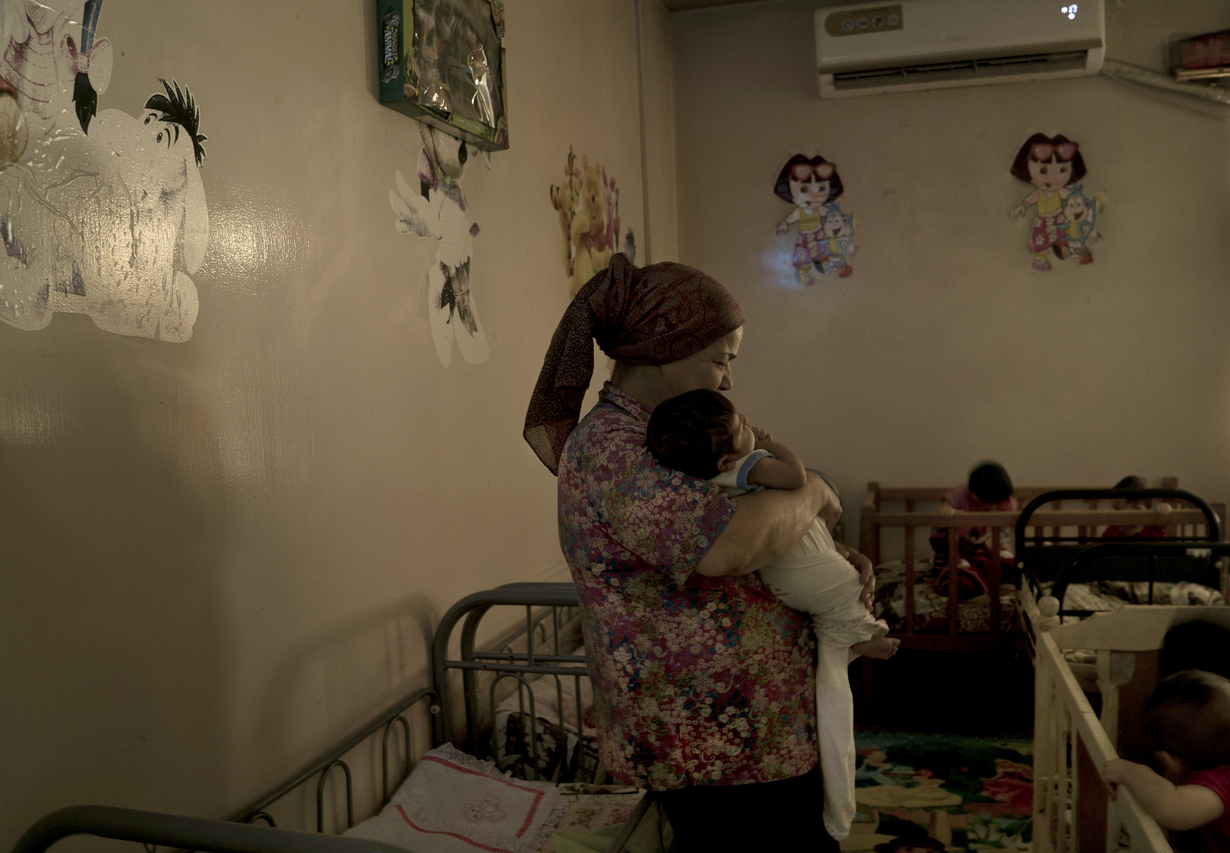 A caretaker cuddles a baby girl named Helen at Salhiya orphanage. Helen was abandoned at the hospital after birth. (AP Photo/Maya Alleruzzo)