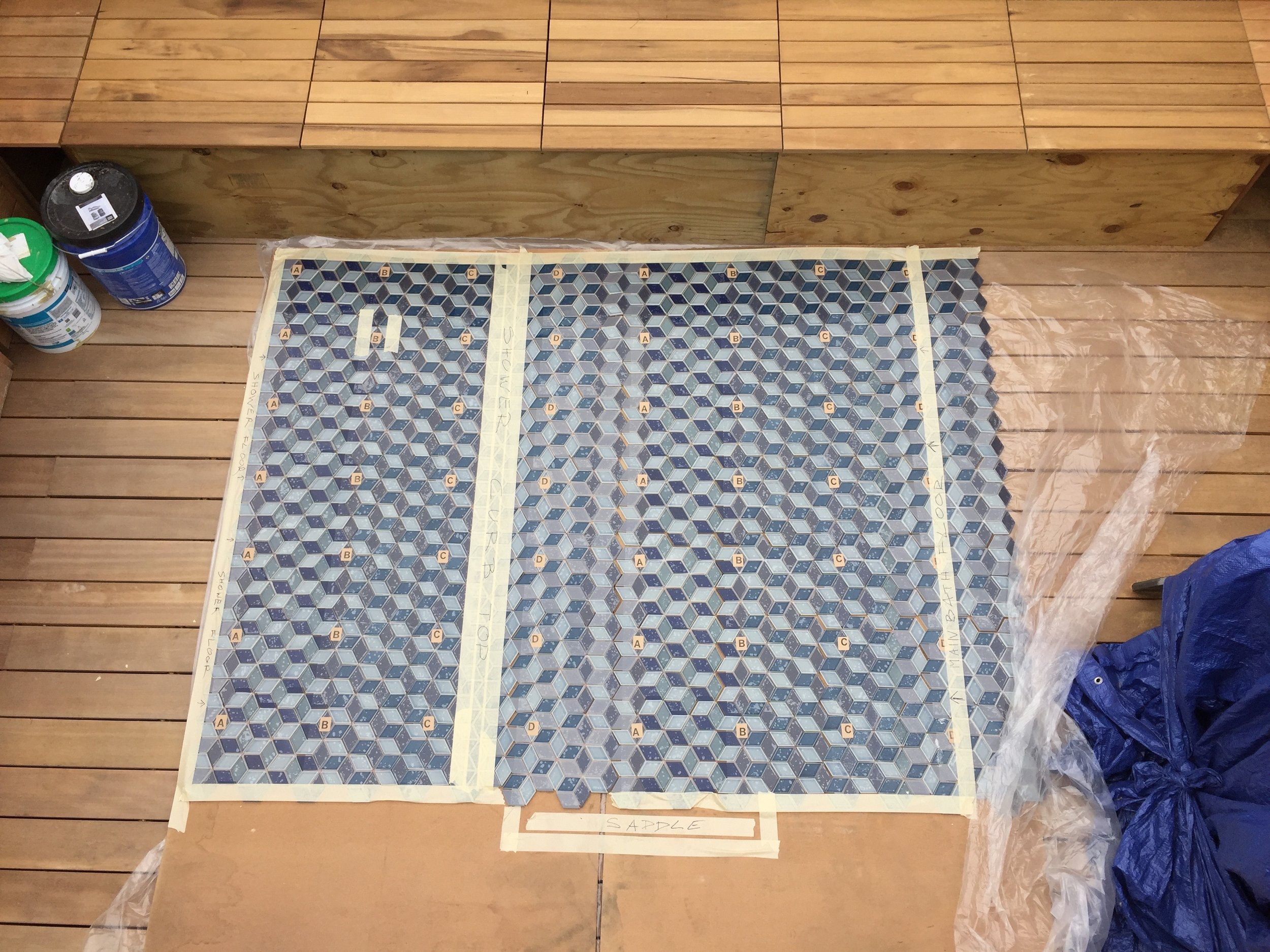 A custom blue mosaic tile is laid out to ensure spacing and accuracy