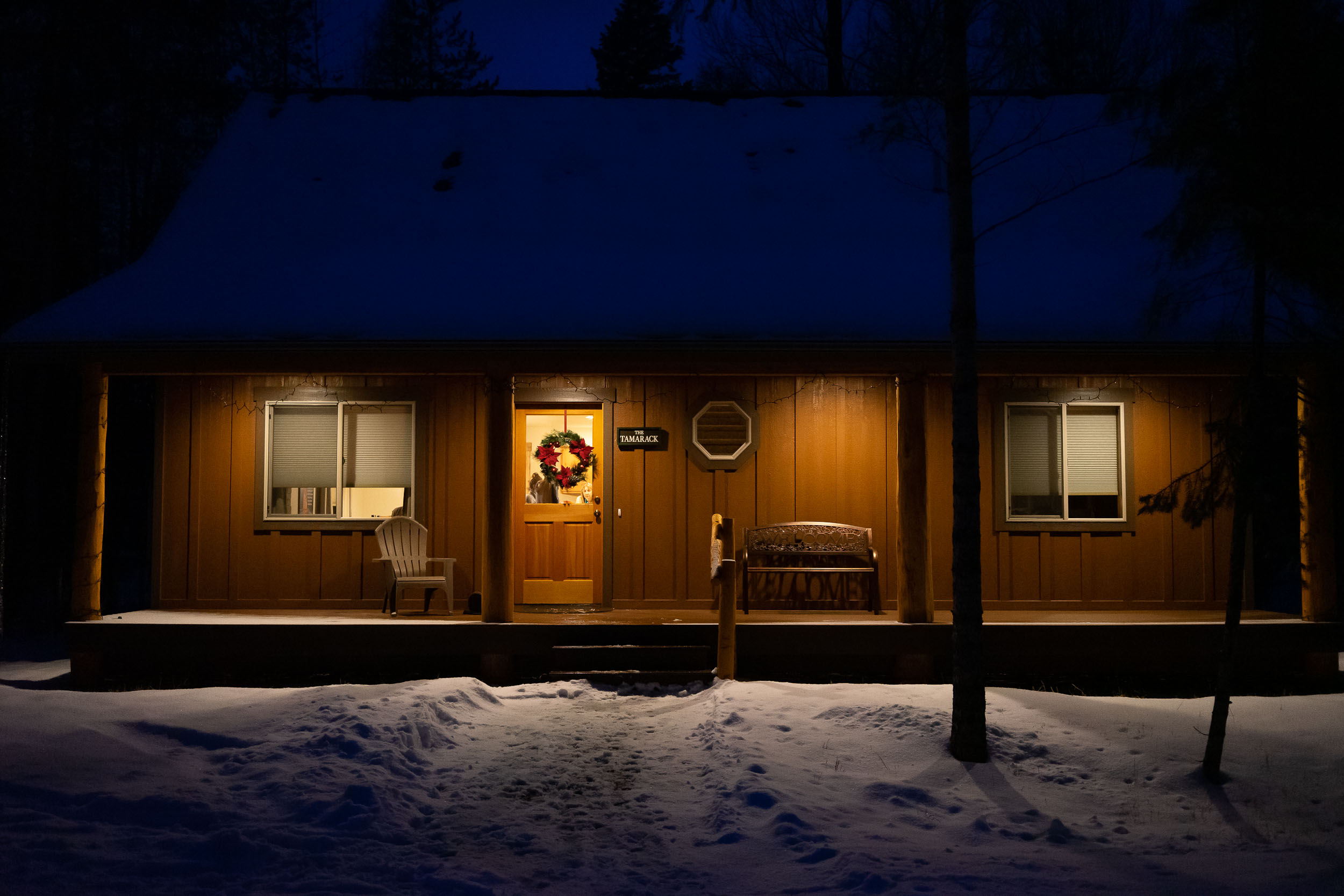 The cutest little snowy cabin near Whitefish, Montana at night.