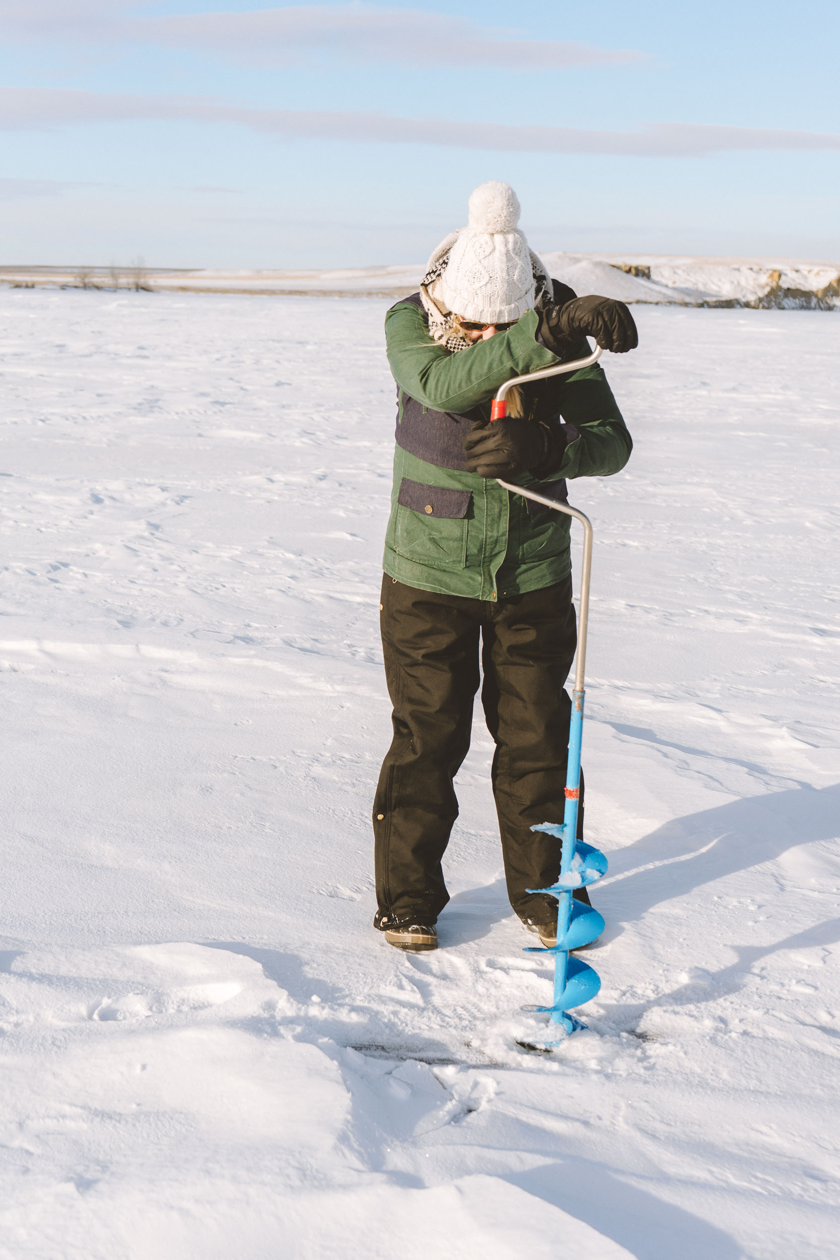 Adventure blogger Bri Sul Ice fishing at Petrolia Lake near Winnett, Montana using a hand auger to dig holes.