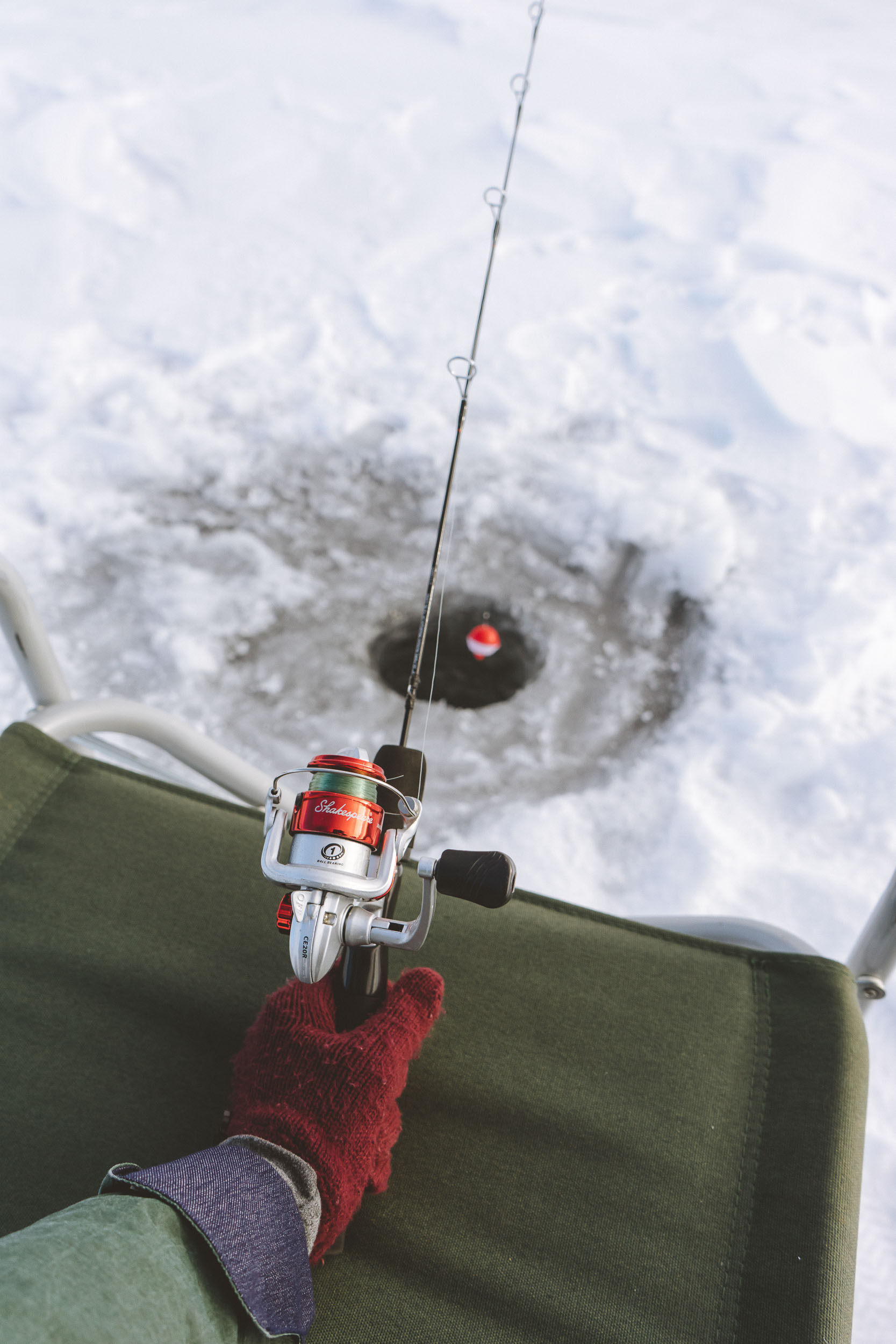 Ice fishing at Petrolia Lake near Winnett, Montana. Beautiful photos takes at Sunrise. Cute folding chair with glove, fishing rod, and bobber.