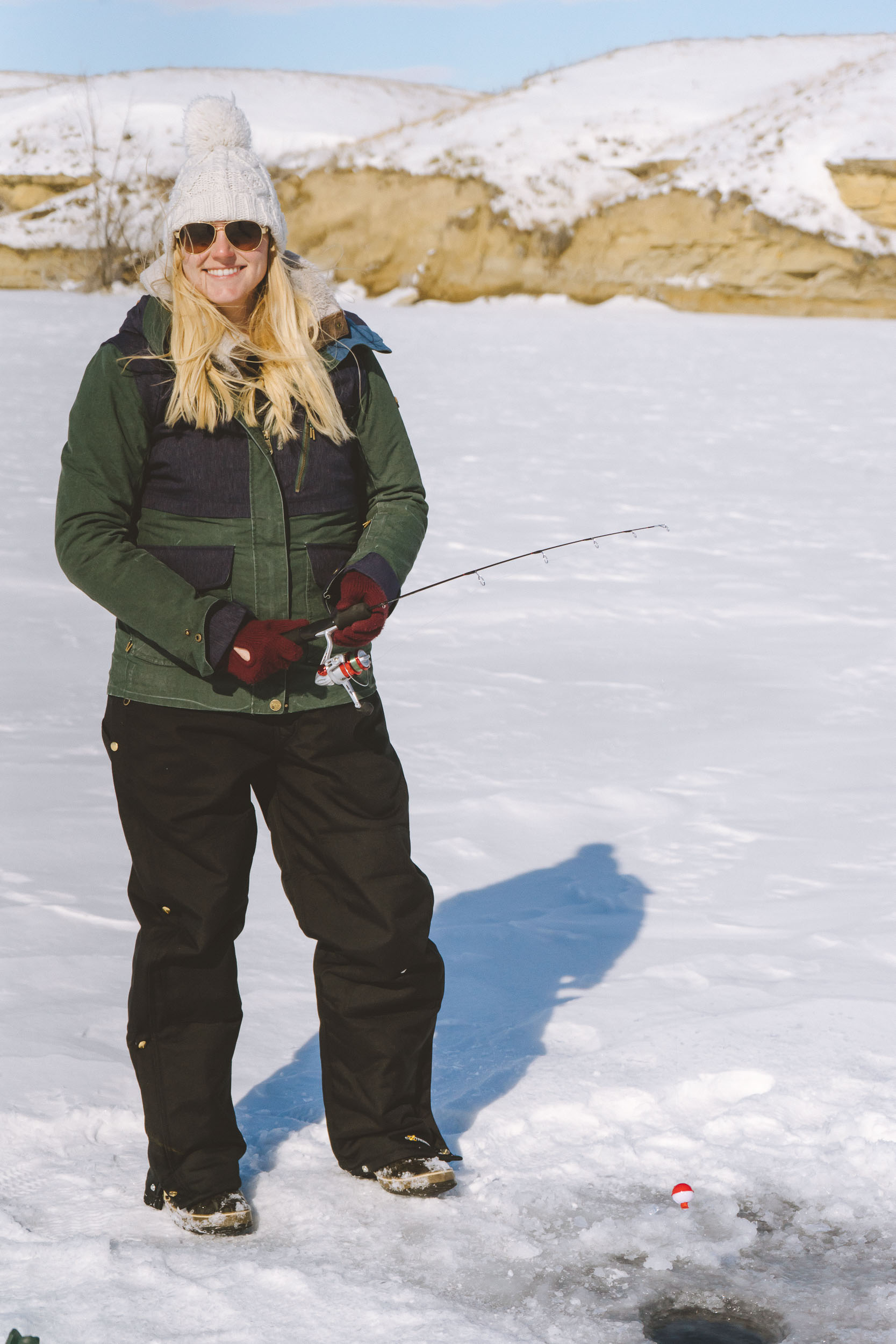 Adventure blogger Bri Sul ice fishing at Petrolia Lake near Winnett, Montana. Wearing Coach sunglasses, a Roxy coat, and the warmest Carhartt bibs.