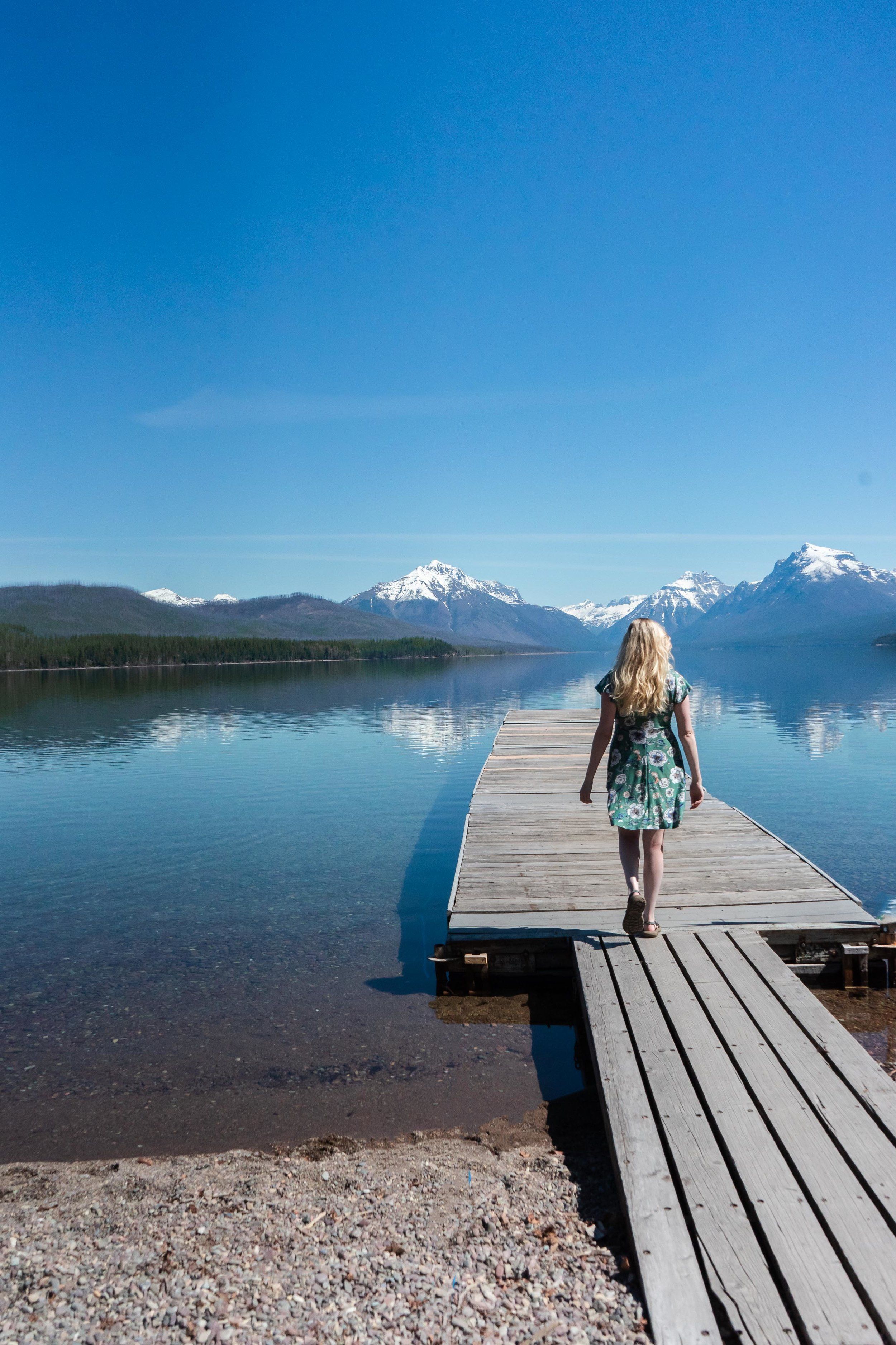 Beautiful snow capped mountains in the spring at Lake McDonald in Glacier National Park near Kalispell and Whitefish, Montana. Bri Sul wearing a floral dress by Stitch Fix and Teva sandals