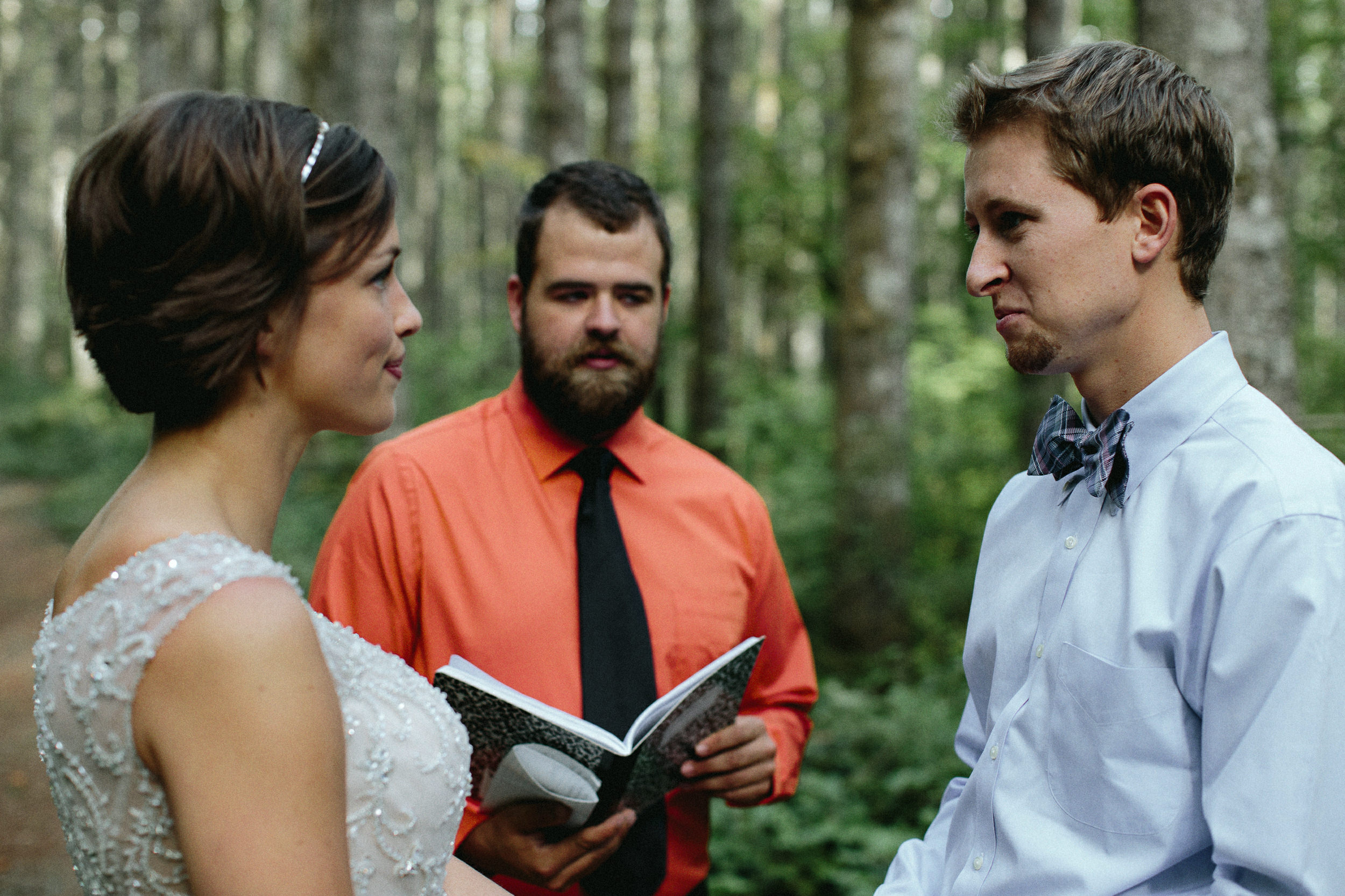 Ibride reading vows during an elopement in a forest cathedral on rattlesnake ridge