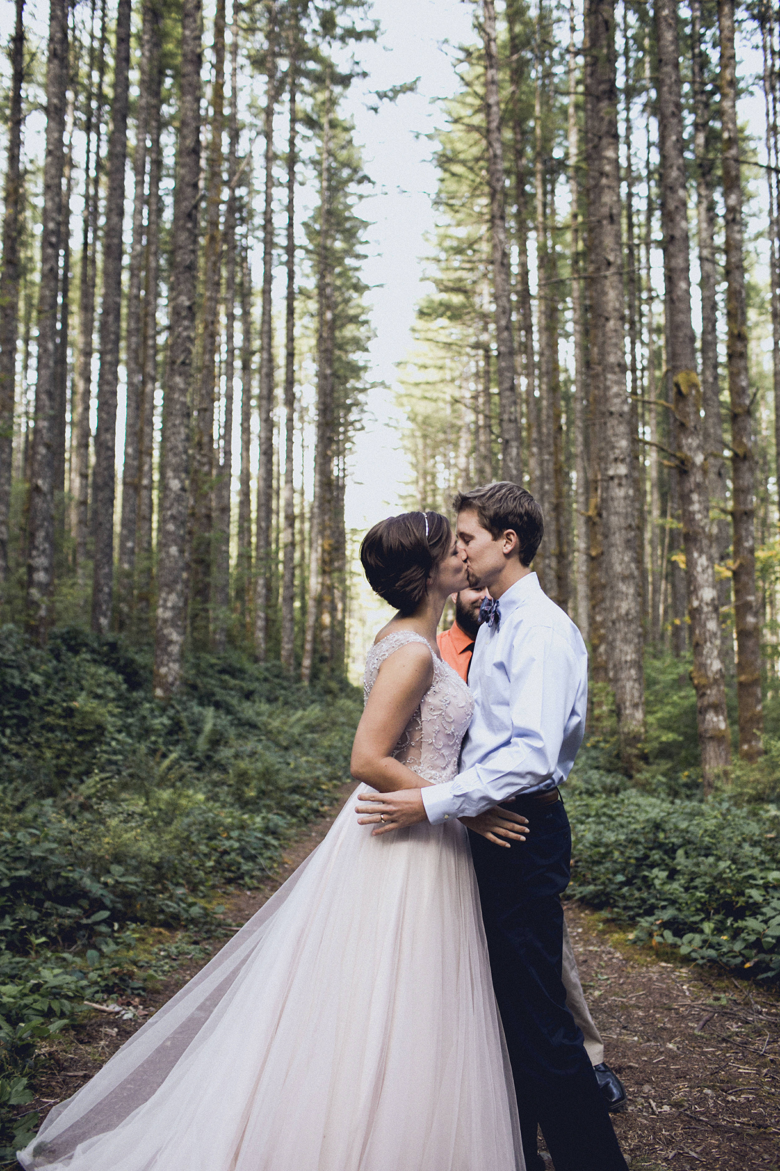 bride and groom kiss during an elopement in a forest cathedral on rattlesnake ridge