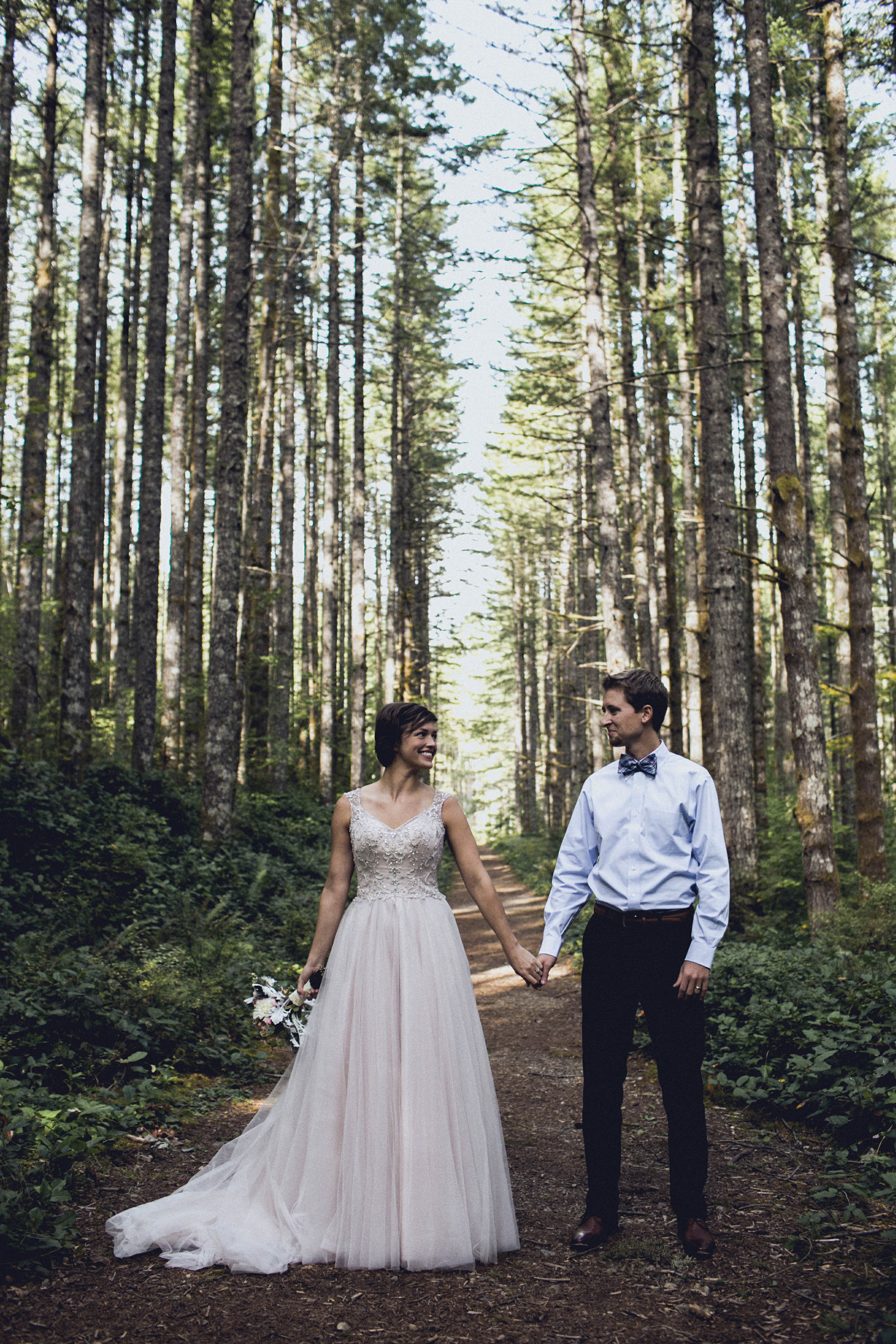 bride and groom pose during an elopement in a forest cathedral on rattlesnake ridge