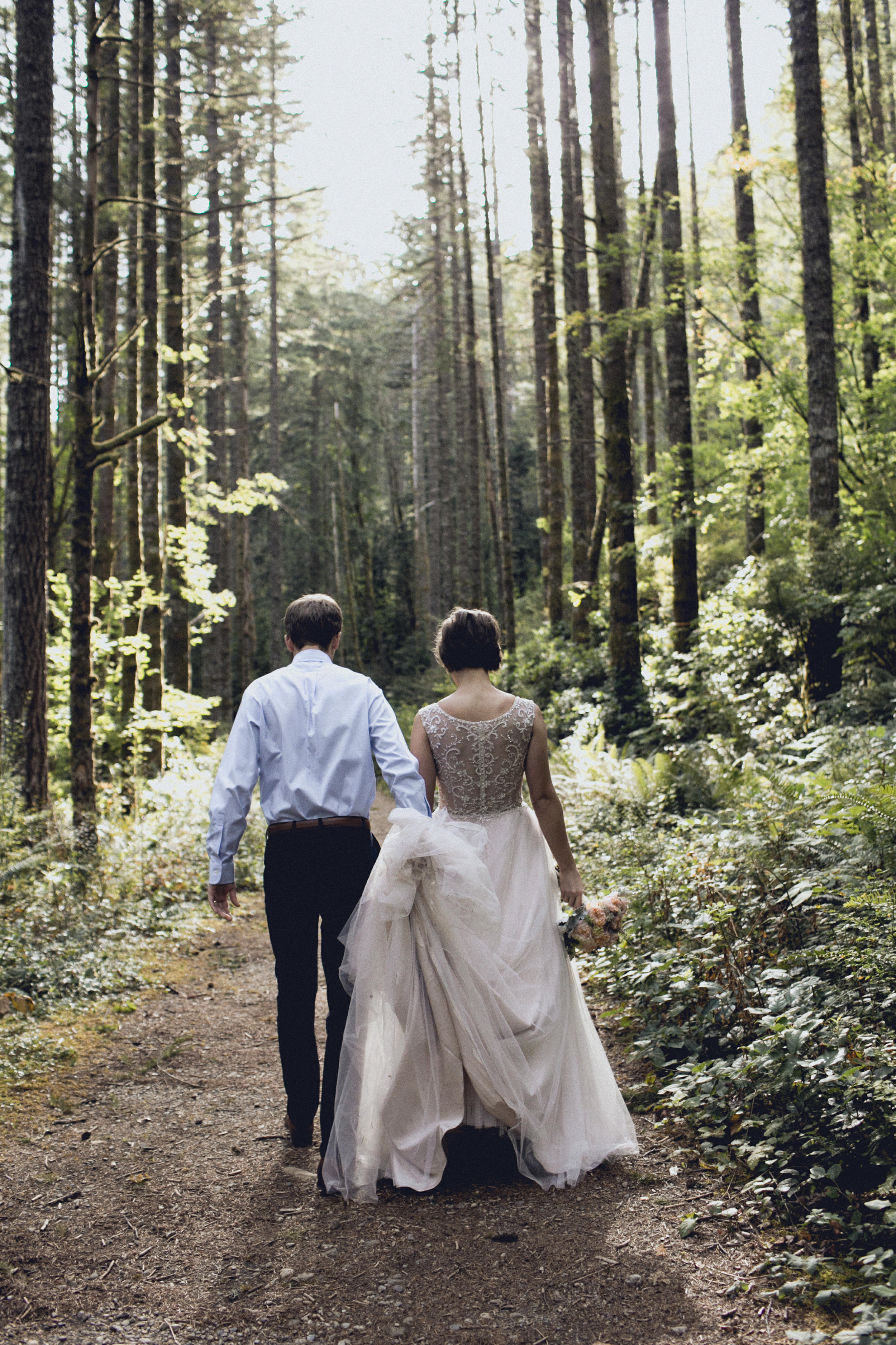bride and groom walk away during an elopement in a forest cathedral on rattlesnake ridge