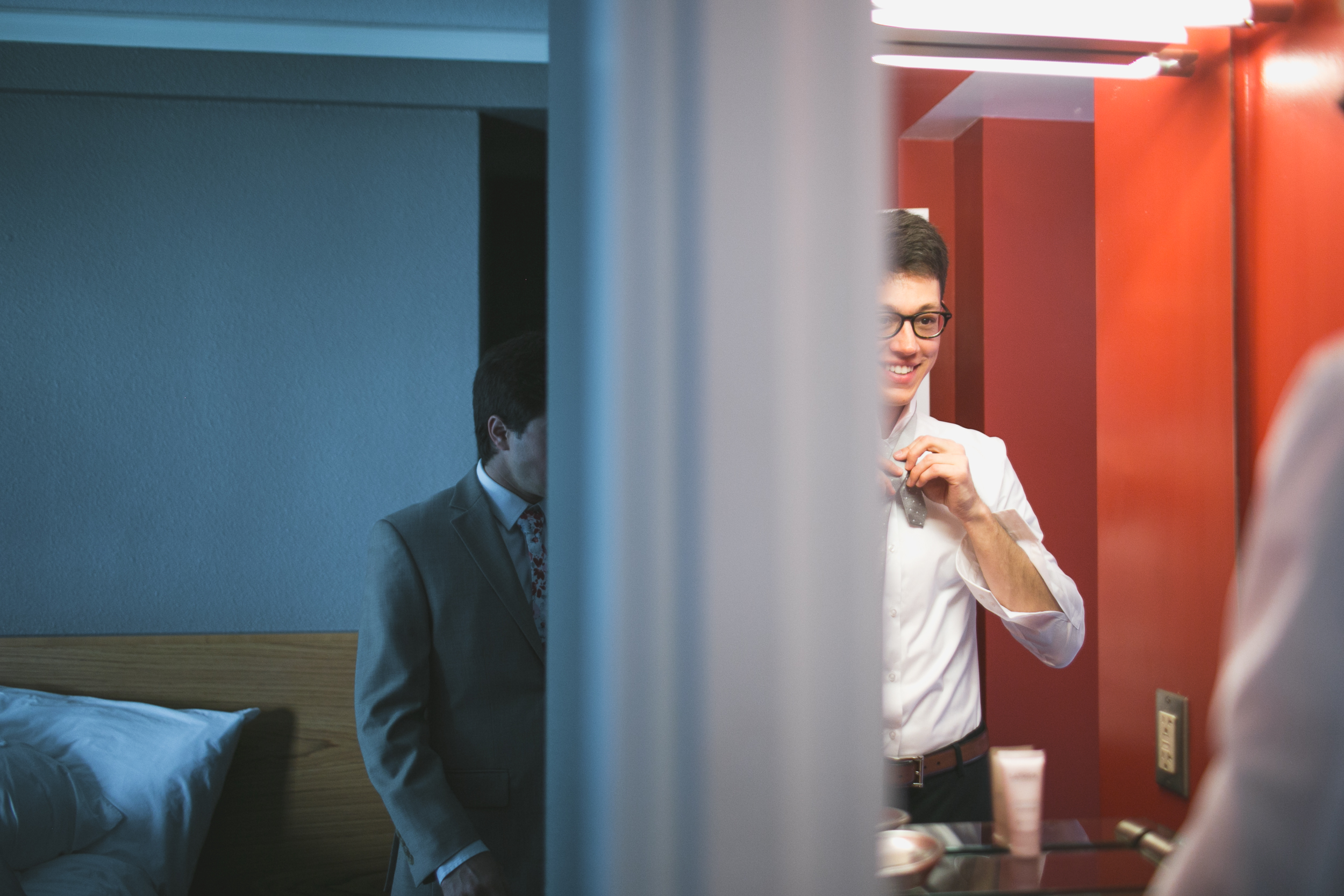 groom getting ready in front of a mirror
