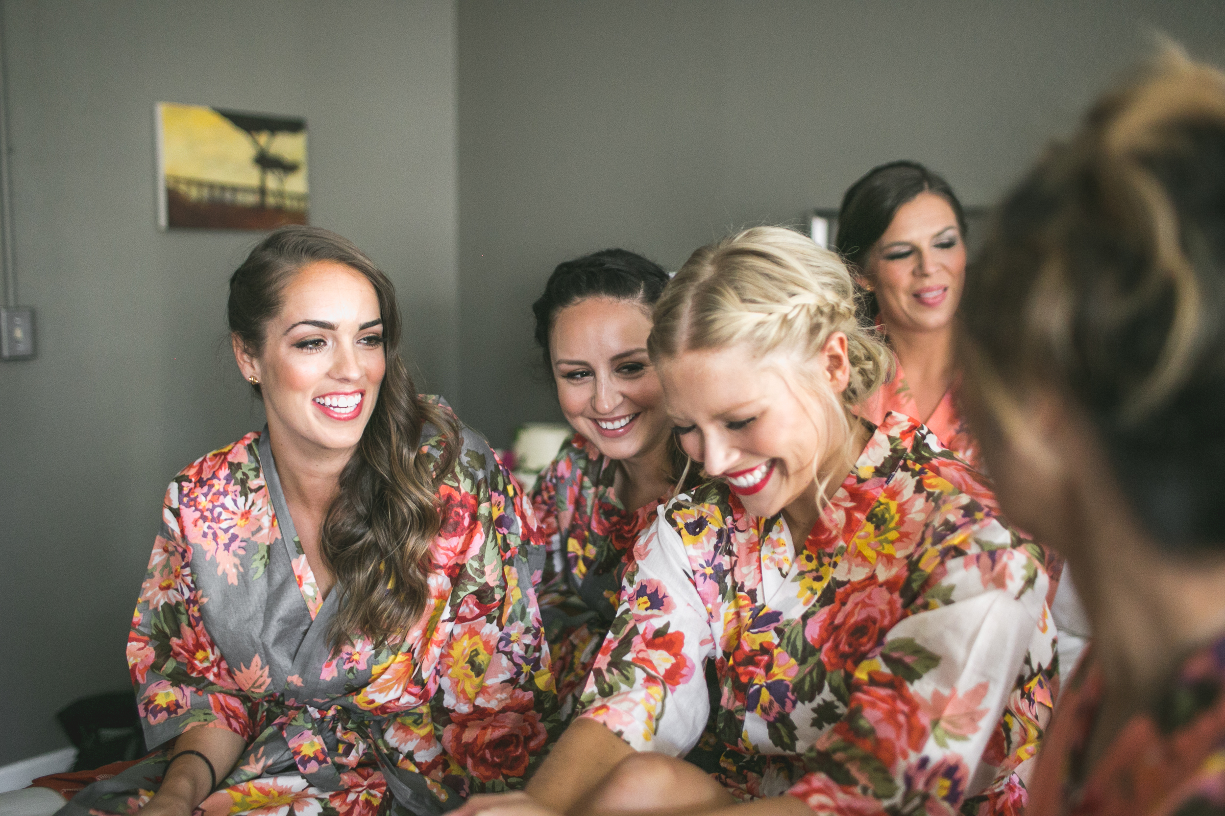 laughing bridesmaids on bed while getting ready