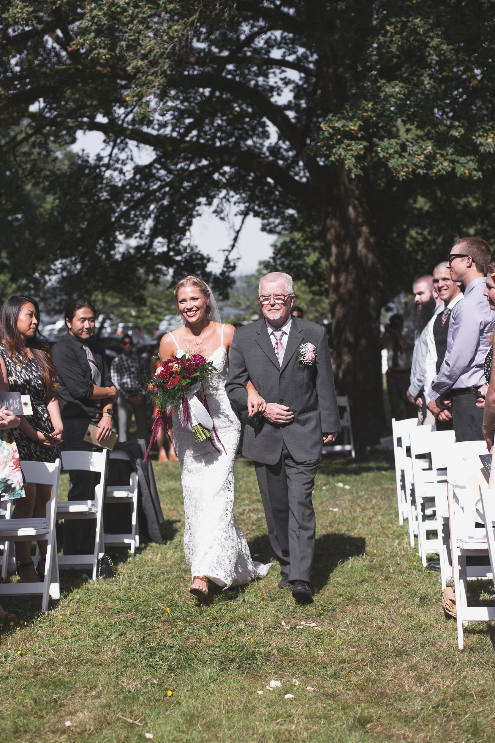father of the bride and bride walking down the aisle at leschi park in seattle