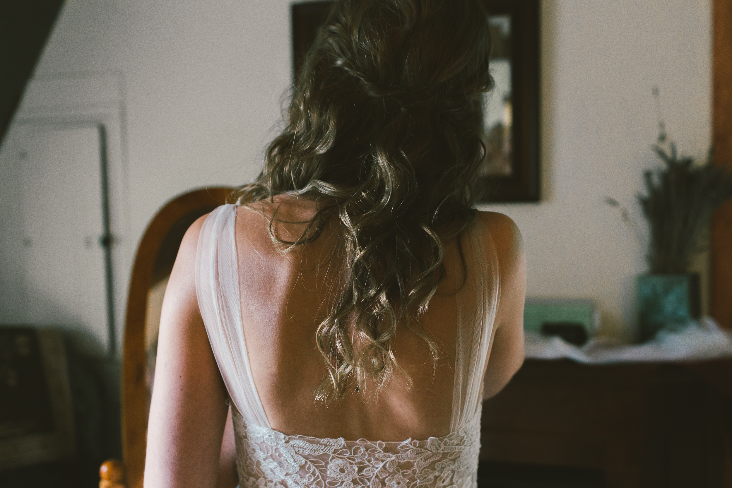 back of bride while she admires herself in the mirror