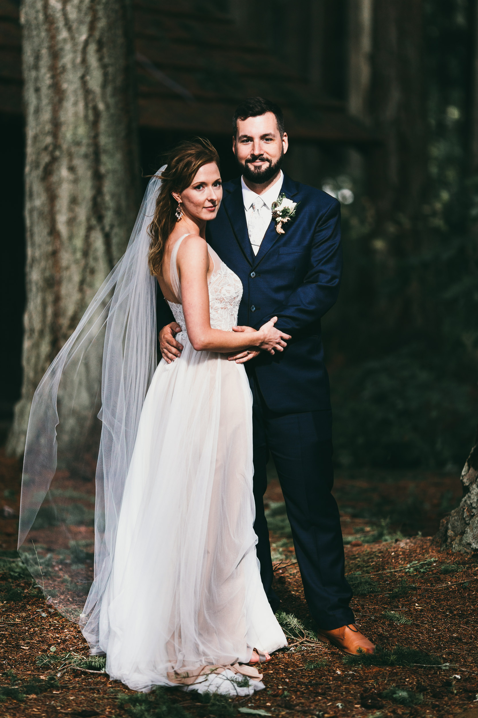 bride and groom in a sunny patch at kitsap memorial state park