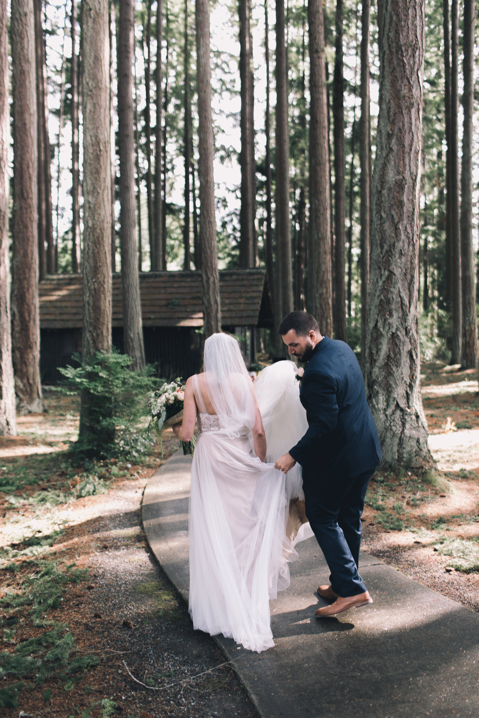 tall trees at kitsap memorial state park with bride and groom walking
