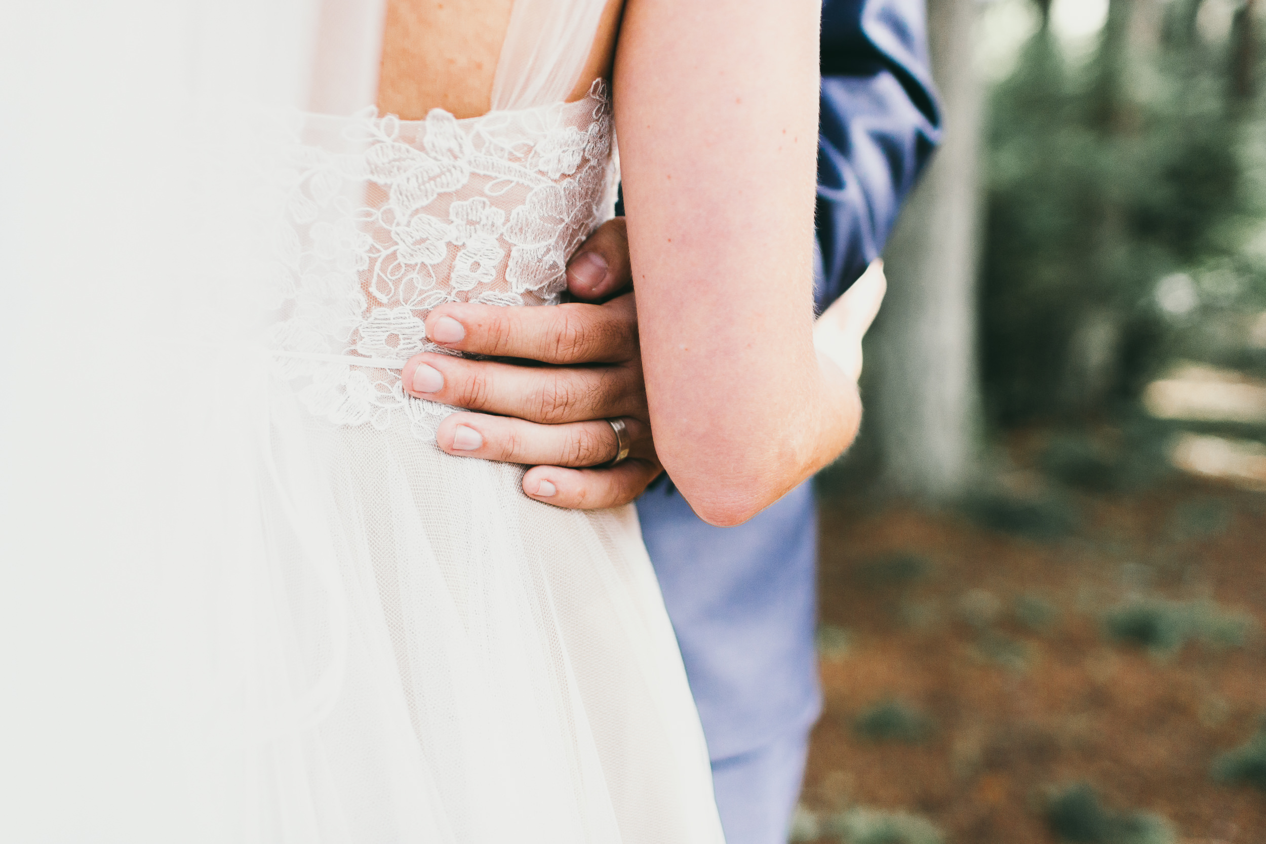 groom tenderly holds bride's waist in forest