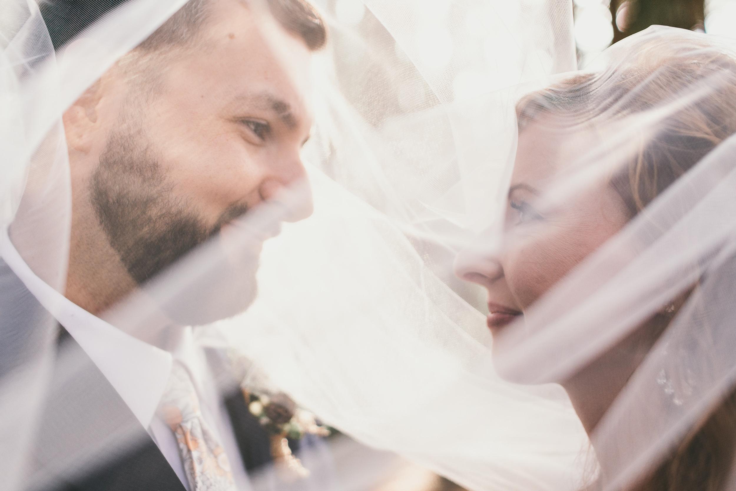 bride and groom both under veil
