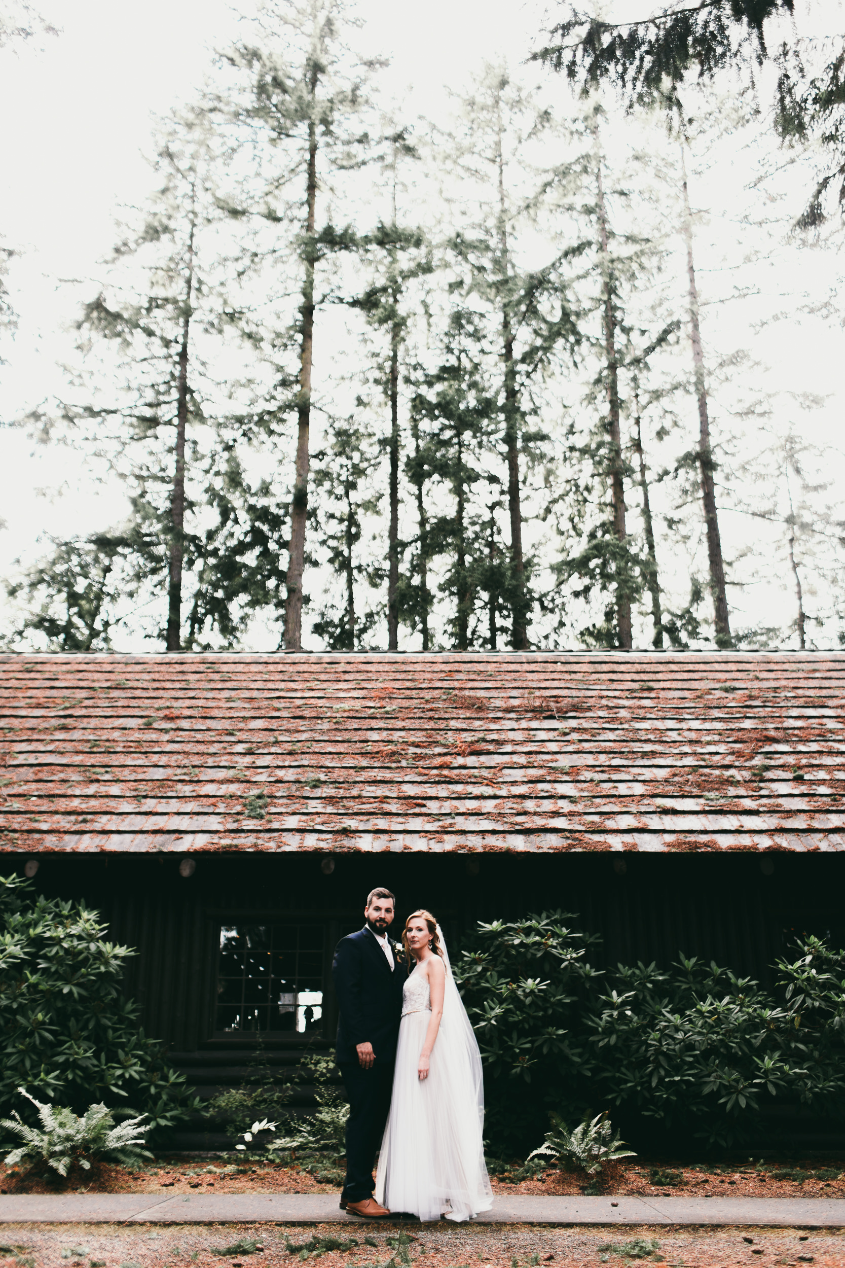 bride and groom in front of log hall at kitsap memorial state park