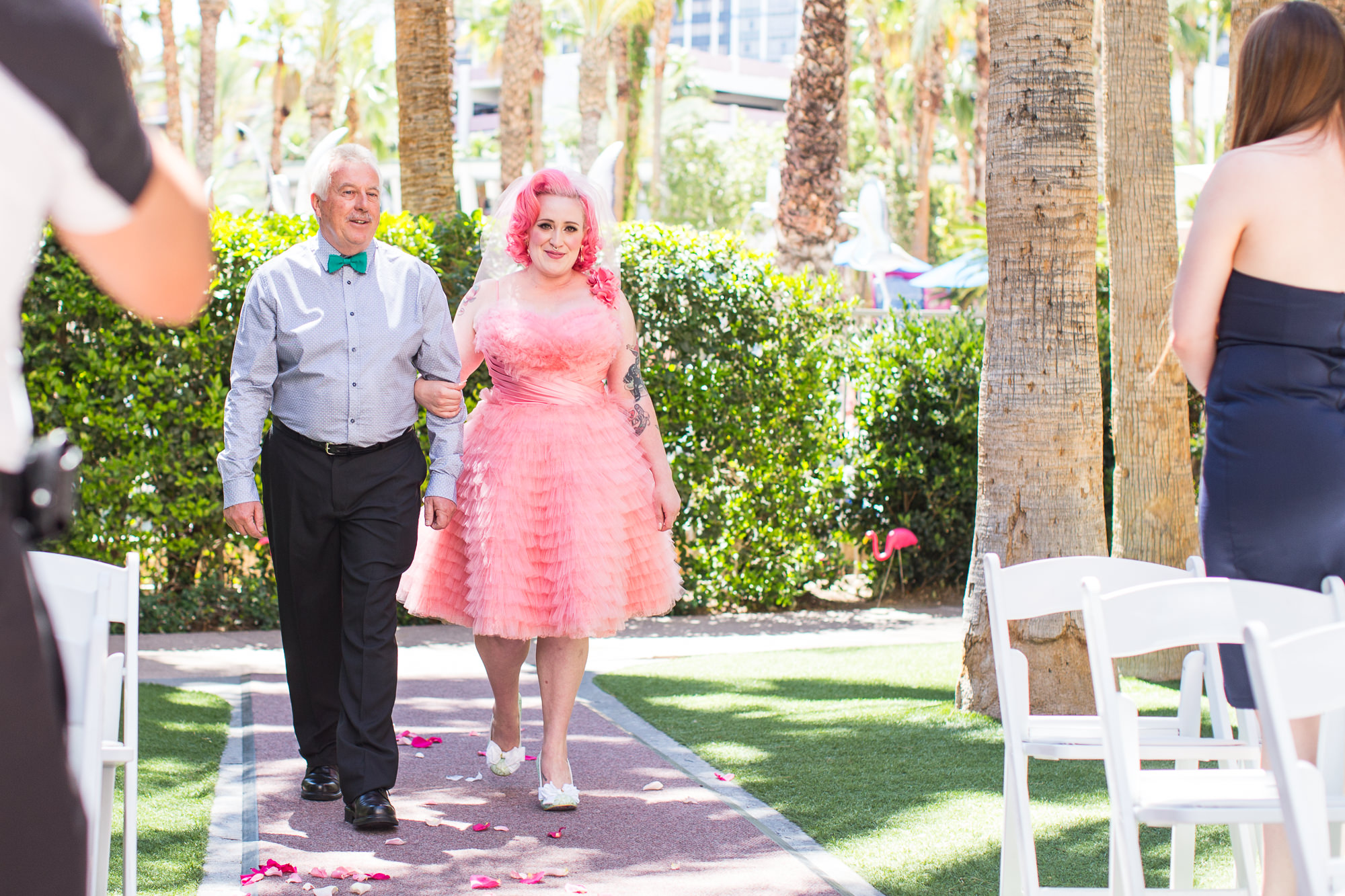 pink bride being walked down the aisle by her father