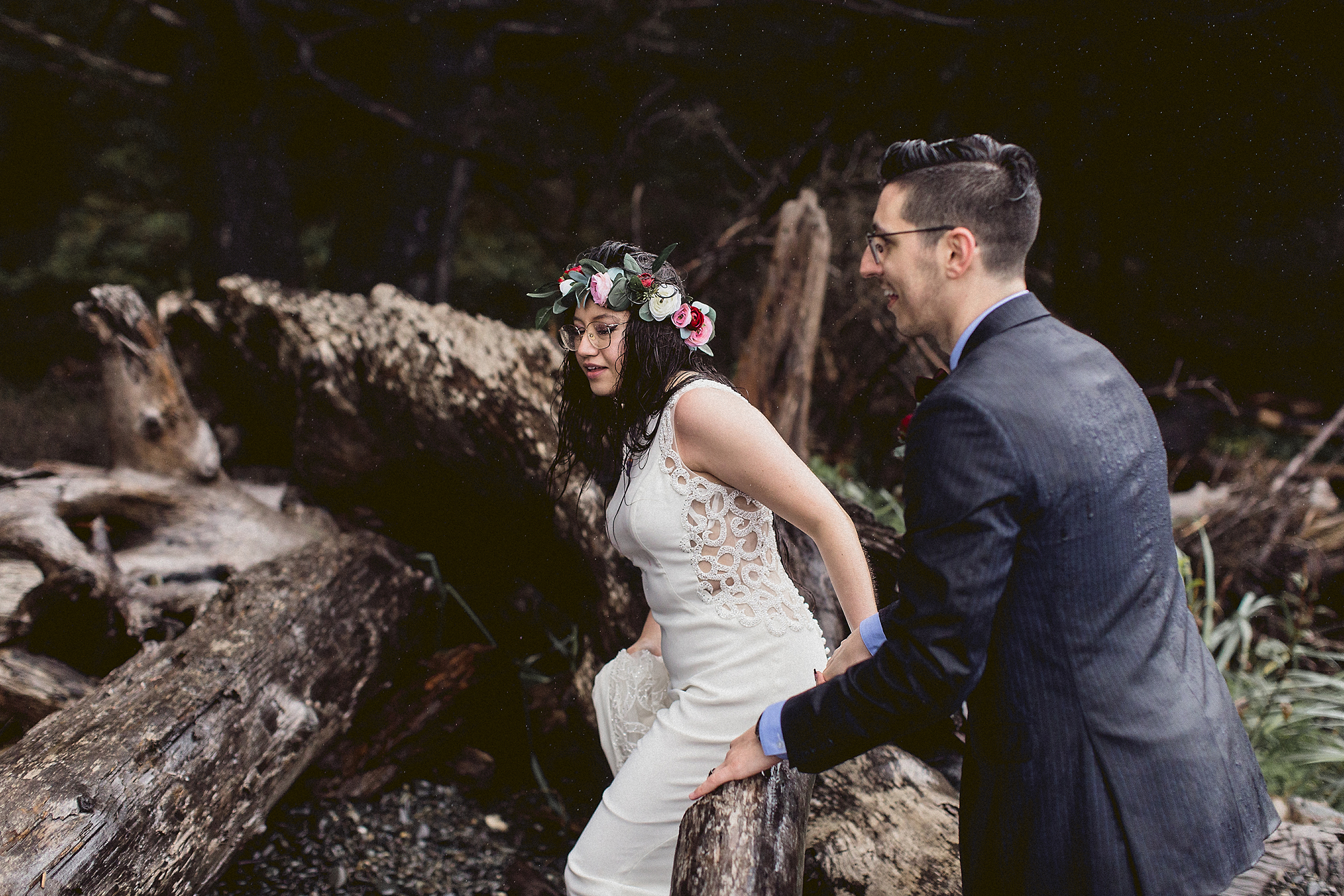 bride and groom walking over driftwood