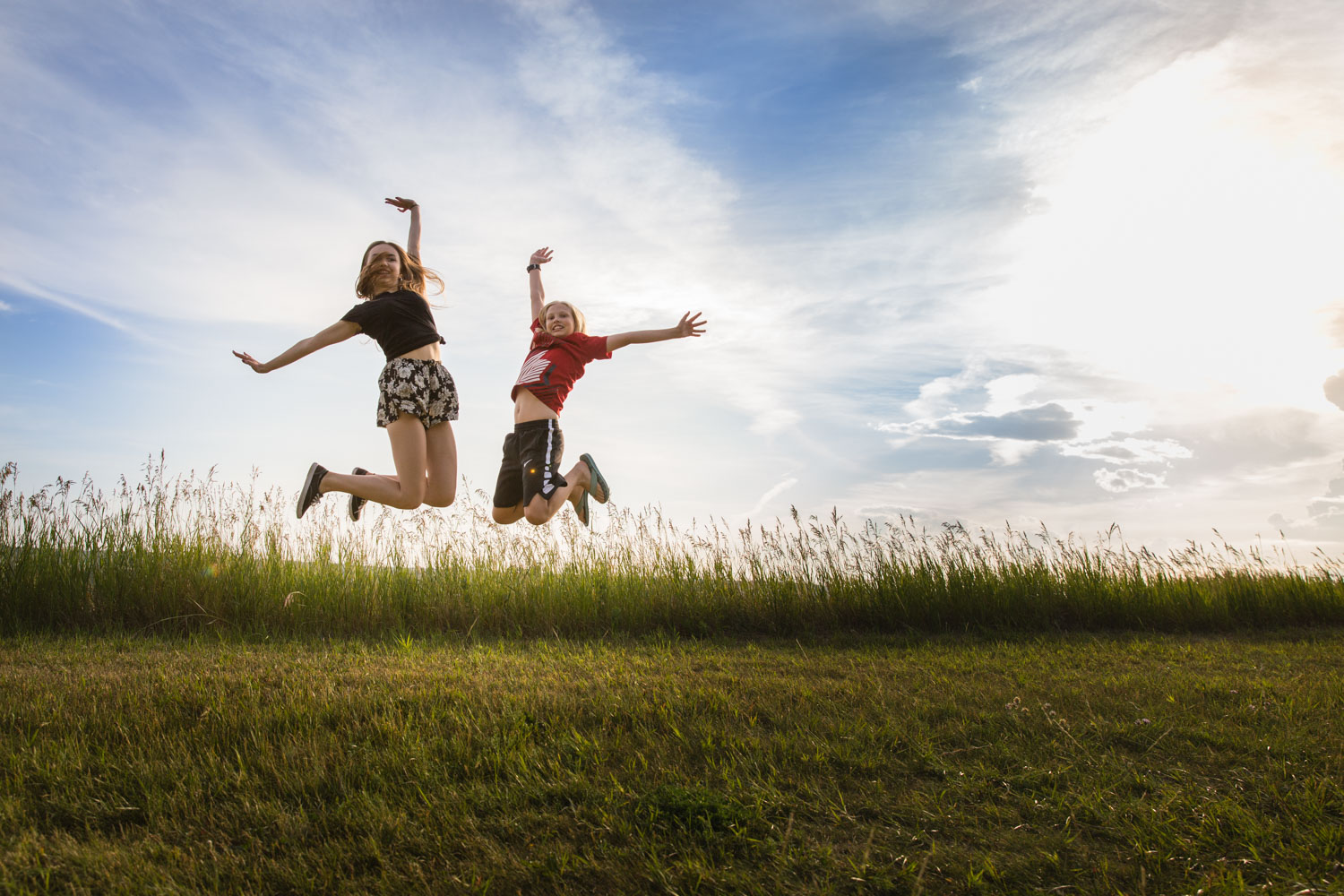 two kids jumping at sunset over a field of green and the clouds behind them.  Summer day