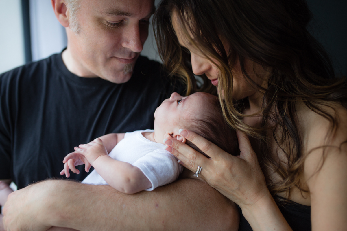 two parents holding a baby mom with long brown wavy hair | Calgary maternity newborn photographer
