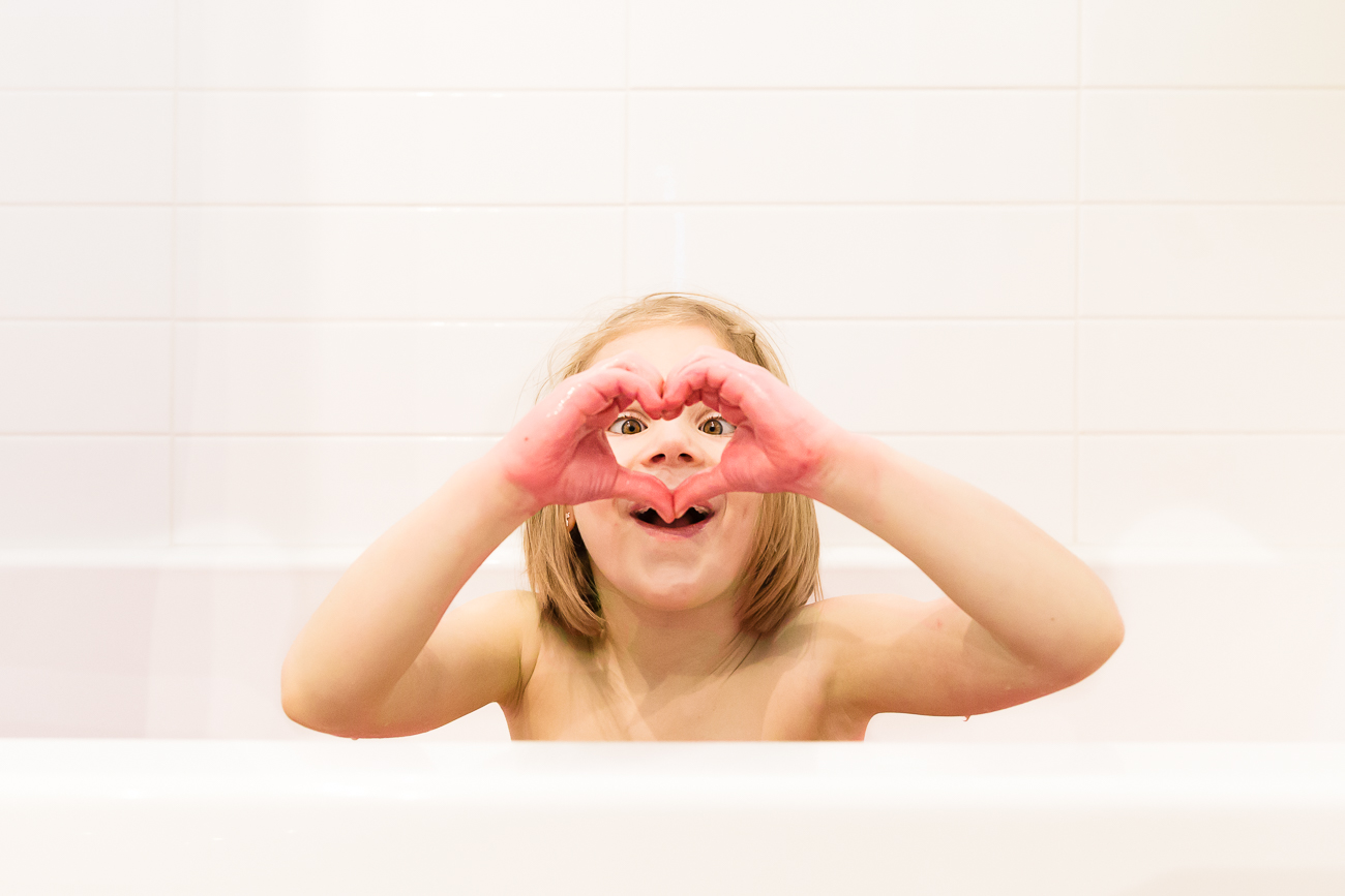 one child in a tub sitting with her hand in a heart over her eyes   Calgary child photographer