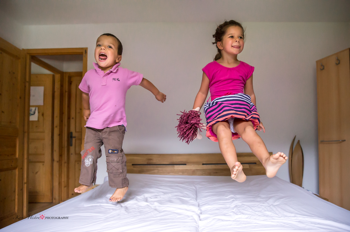 two kids jumping on the bed and playing around in pink clothes   Calgary child photographer