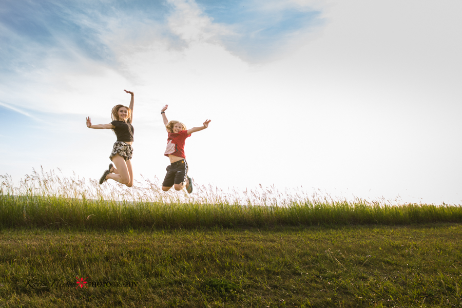 two kids jumping on a summer day in a green field with blue sky behind them   Calgary child photographer