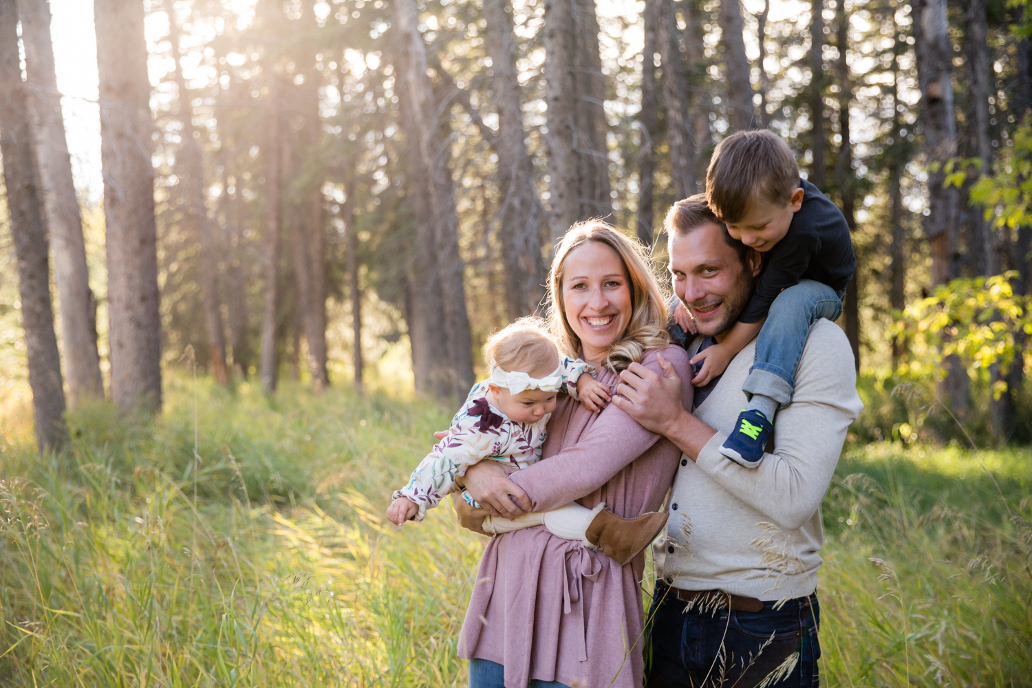 portrait of a family in a green field together looking at the camera | Calgary family photographer