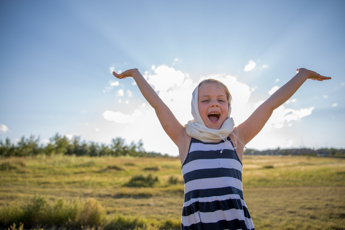child with her arms up in a green field with sun behind her   Calgary child photographer