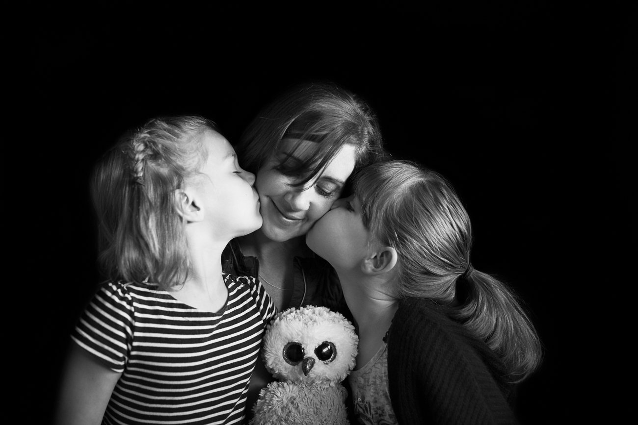 black and white image of two girls kissing their mom on the cheek | Calgary family photographer