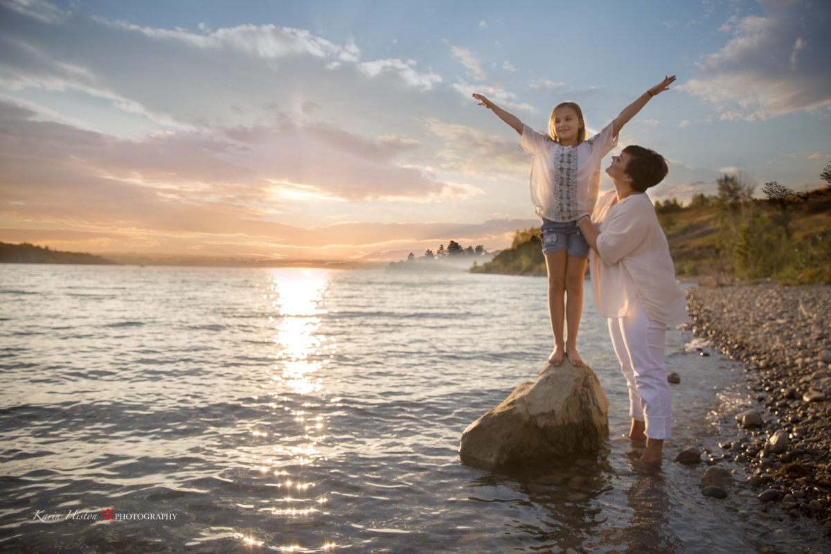 at a lake with the sunset with a child on a rock and mom holding on | Calgary family photographer
