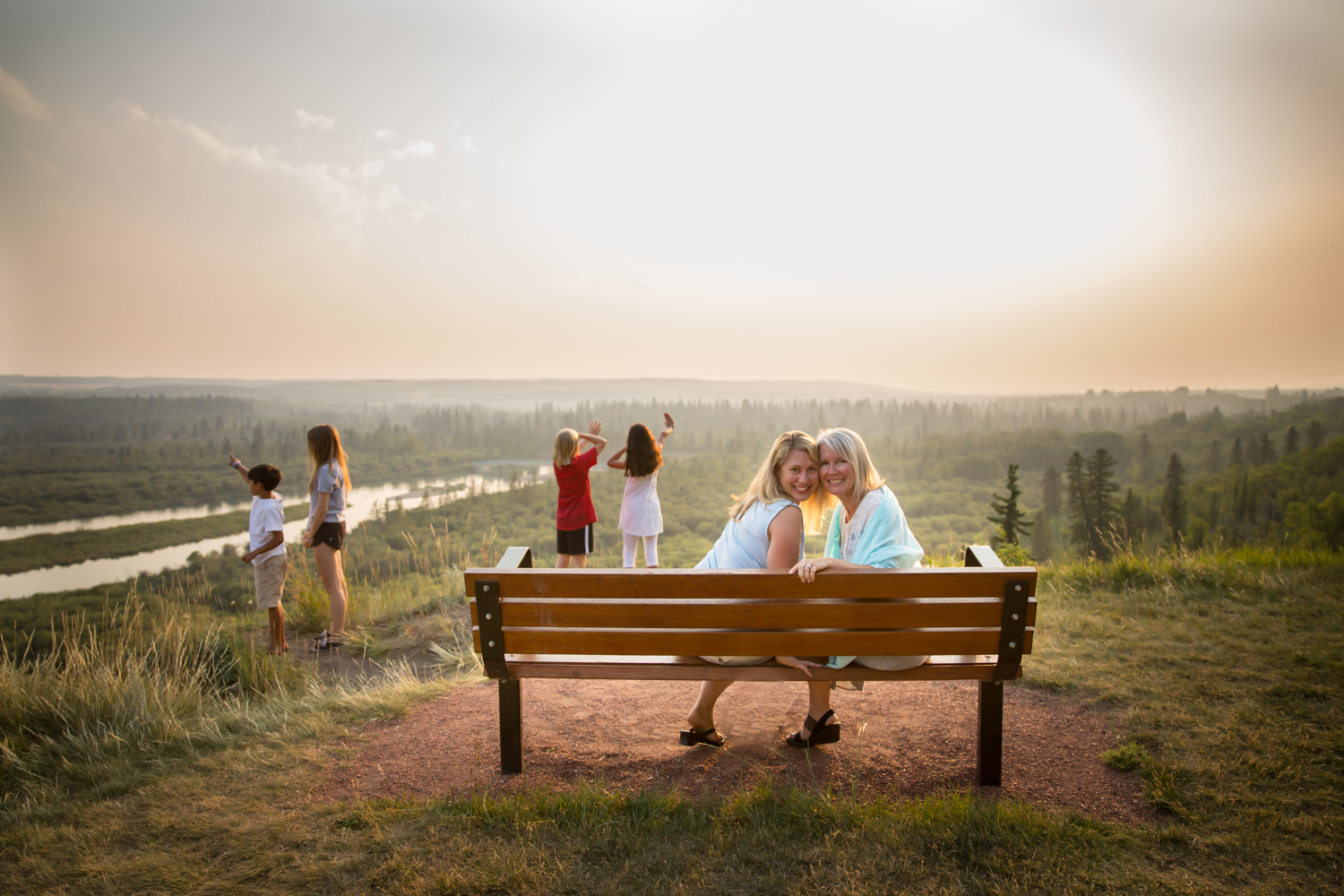 two sisters on a bench with their kids behind them in the sunset | Calgary family photographer