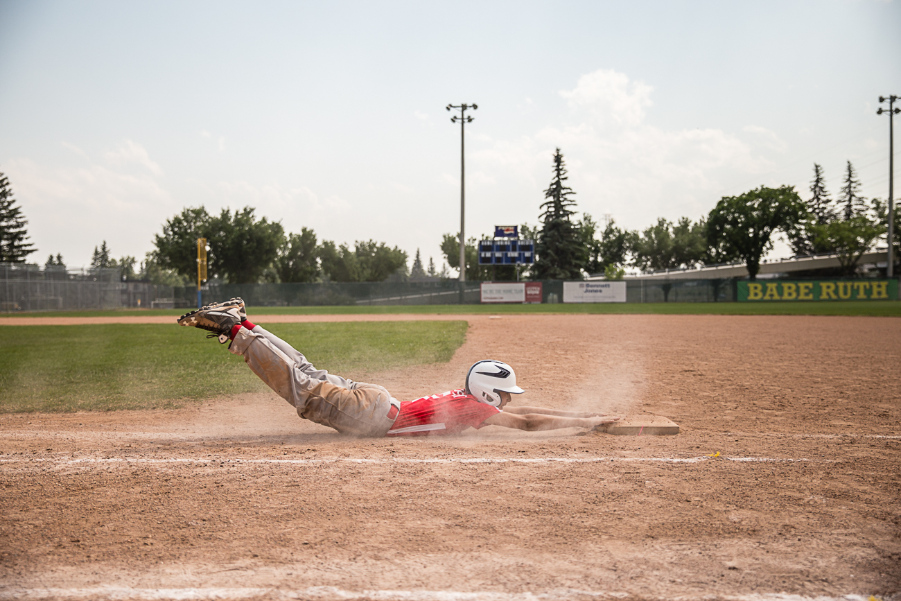 a baseball player coming into the home plate with dust everywhere   Calgary child photographer