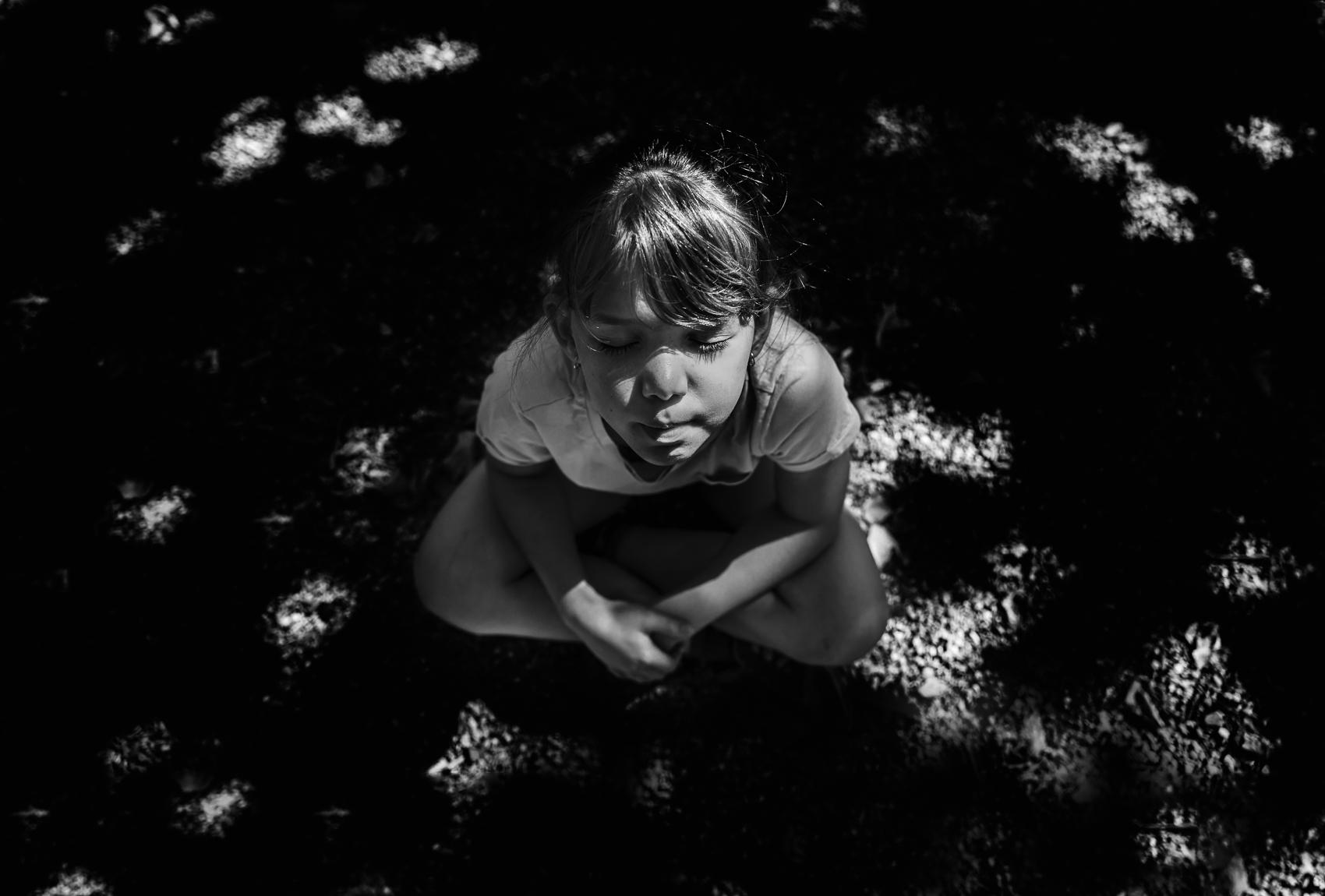girl sitting in dappled light