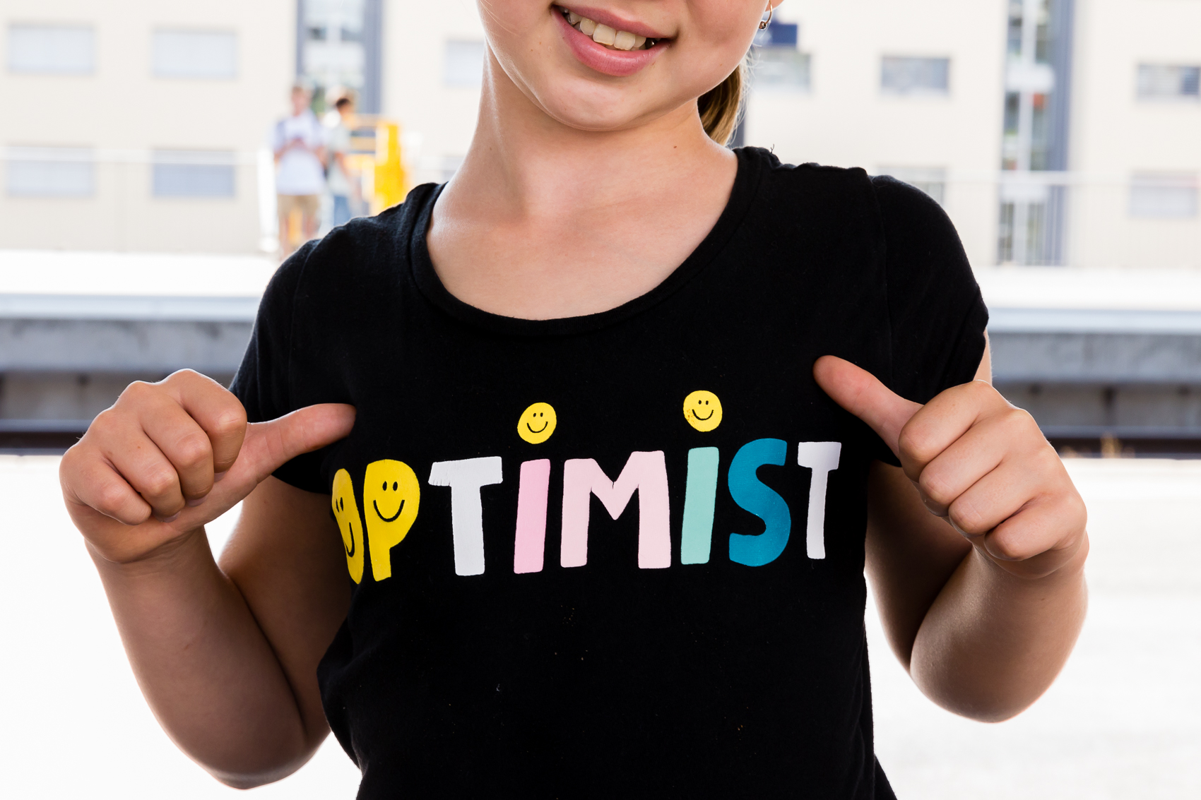 girls with optimist on her shirt thumbs pointing to it