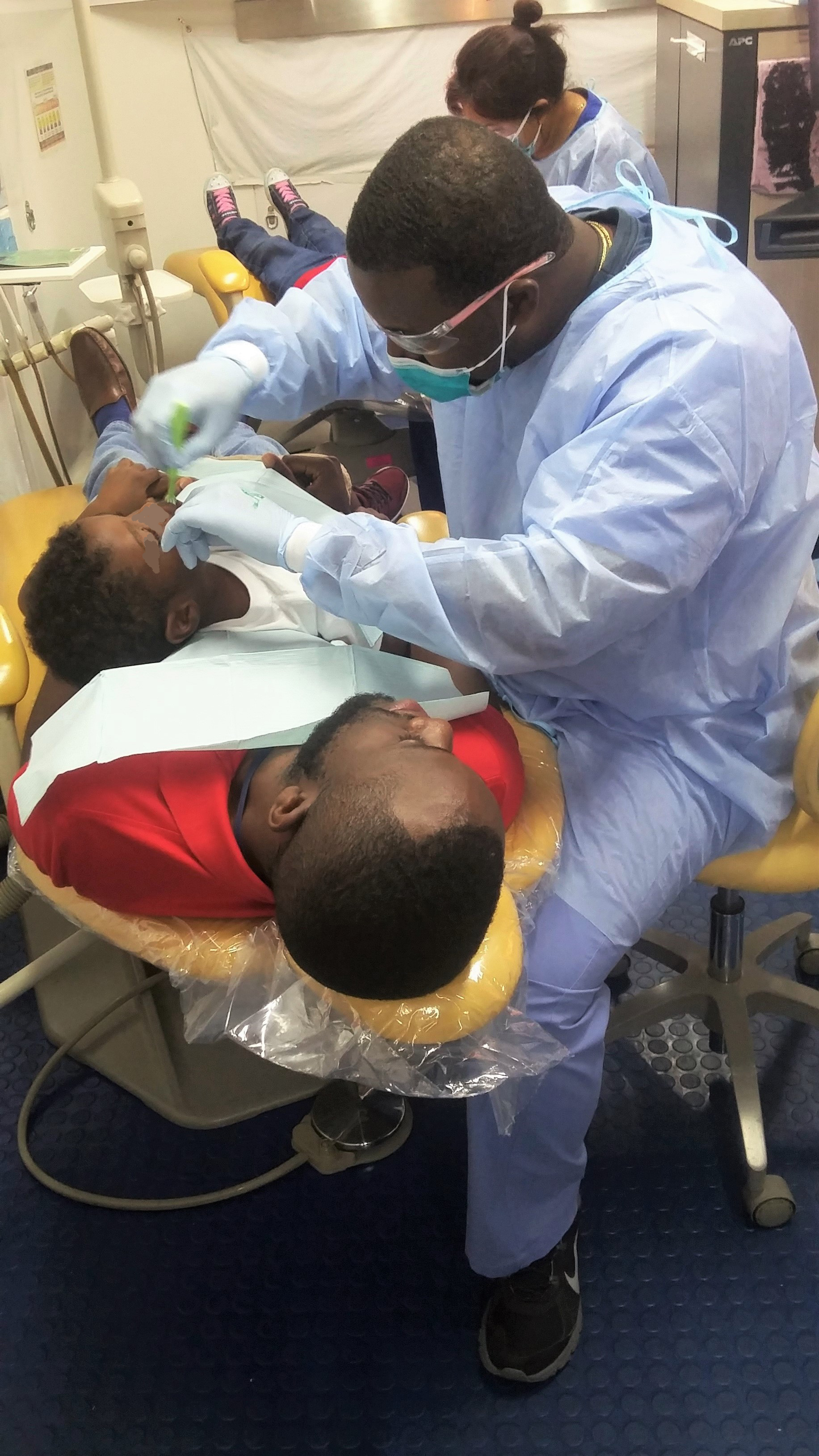 Hat's off to Curtiss Walker, a case manager in Manatee County, for going the extra mile by assuring the little man on his lap did not need to feel nervous about the dentist. Dr. Jerry Chery, DDS, works on the little man as he get's an exam and cleaning.