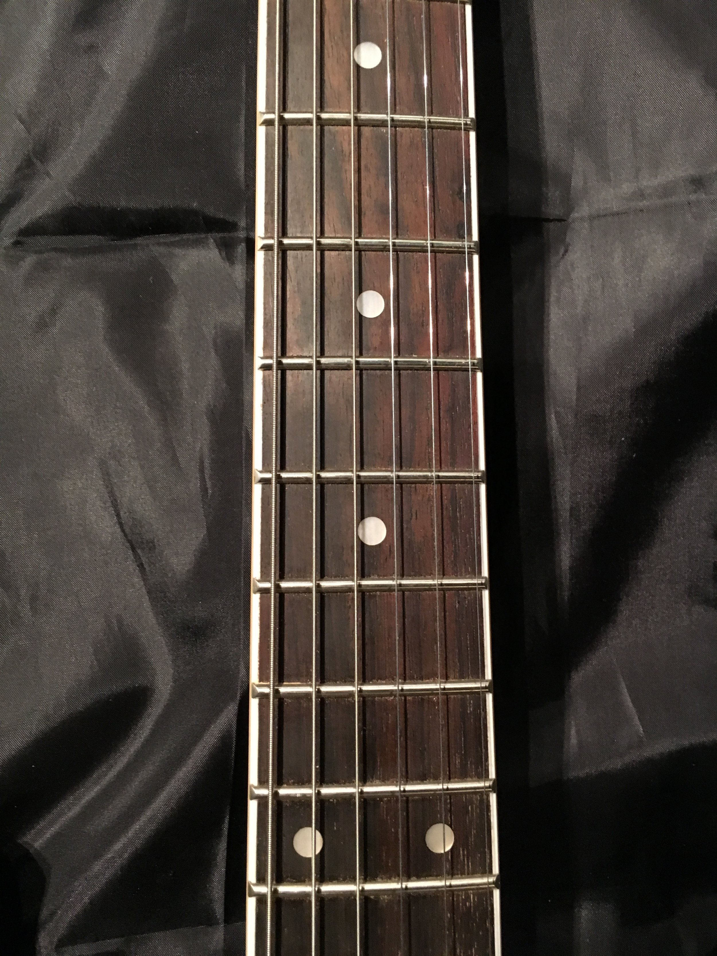 Rosewood fingerboard with binding on the edges.  Jumbo frets.