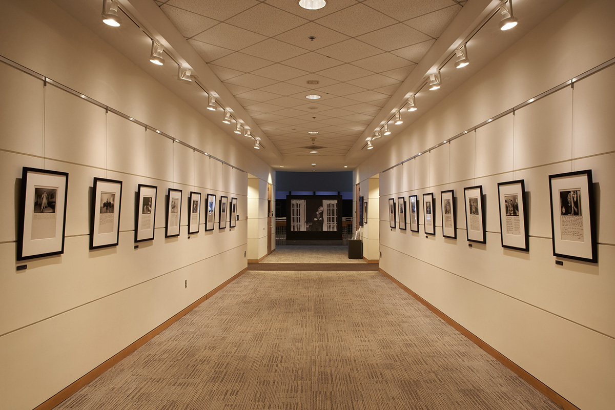 View of gallery showing framed photographs with enlarged photograph as central focal point in the distance.