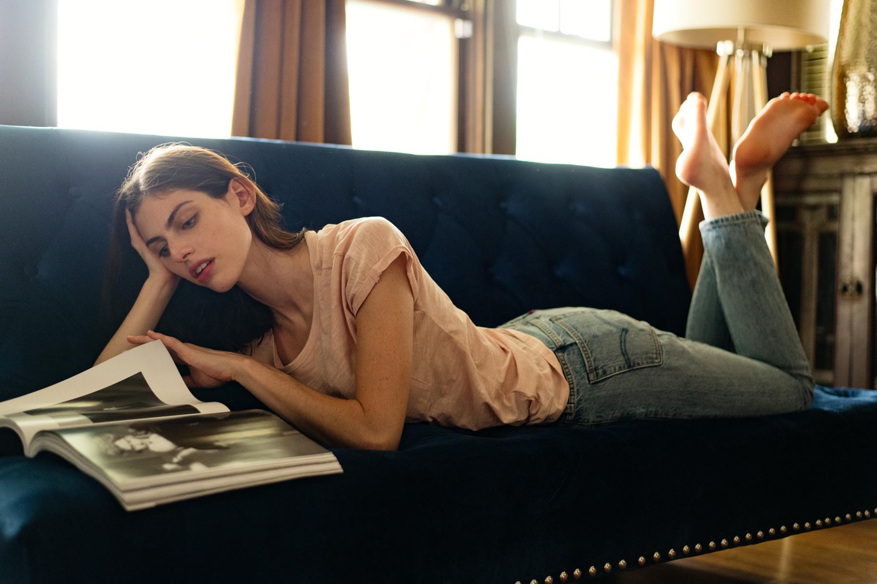 woman-reads-magazine-on-sofa-backlit.jpg