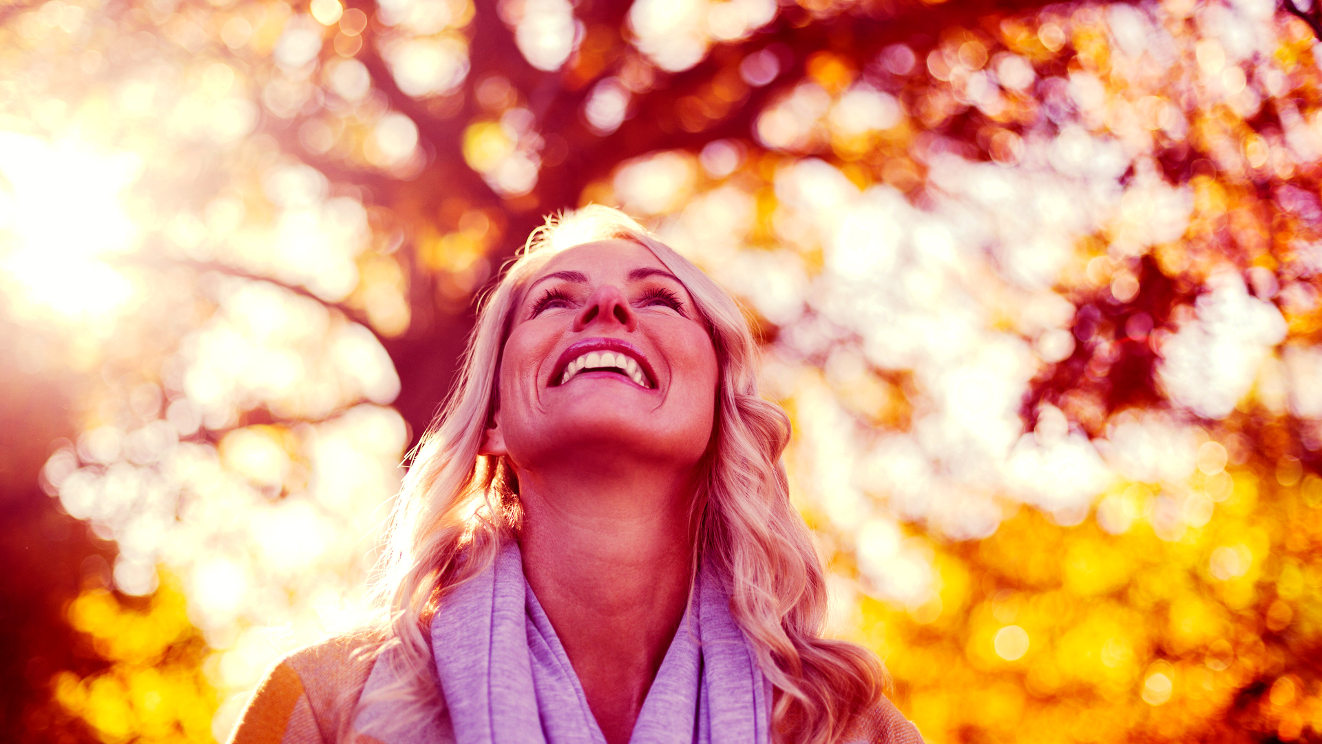 Woman looking up at trees with happiness