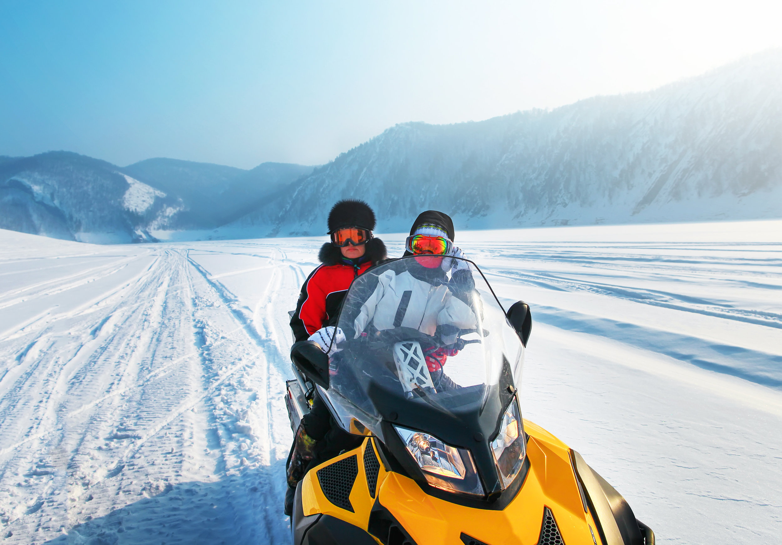 Man and woman riding on snowmobile