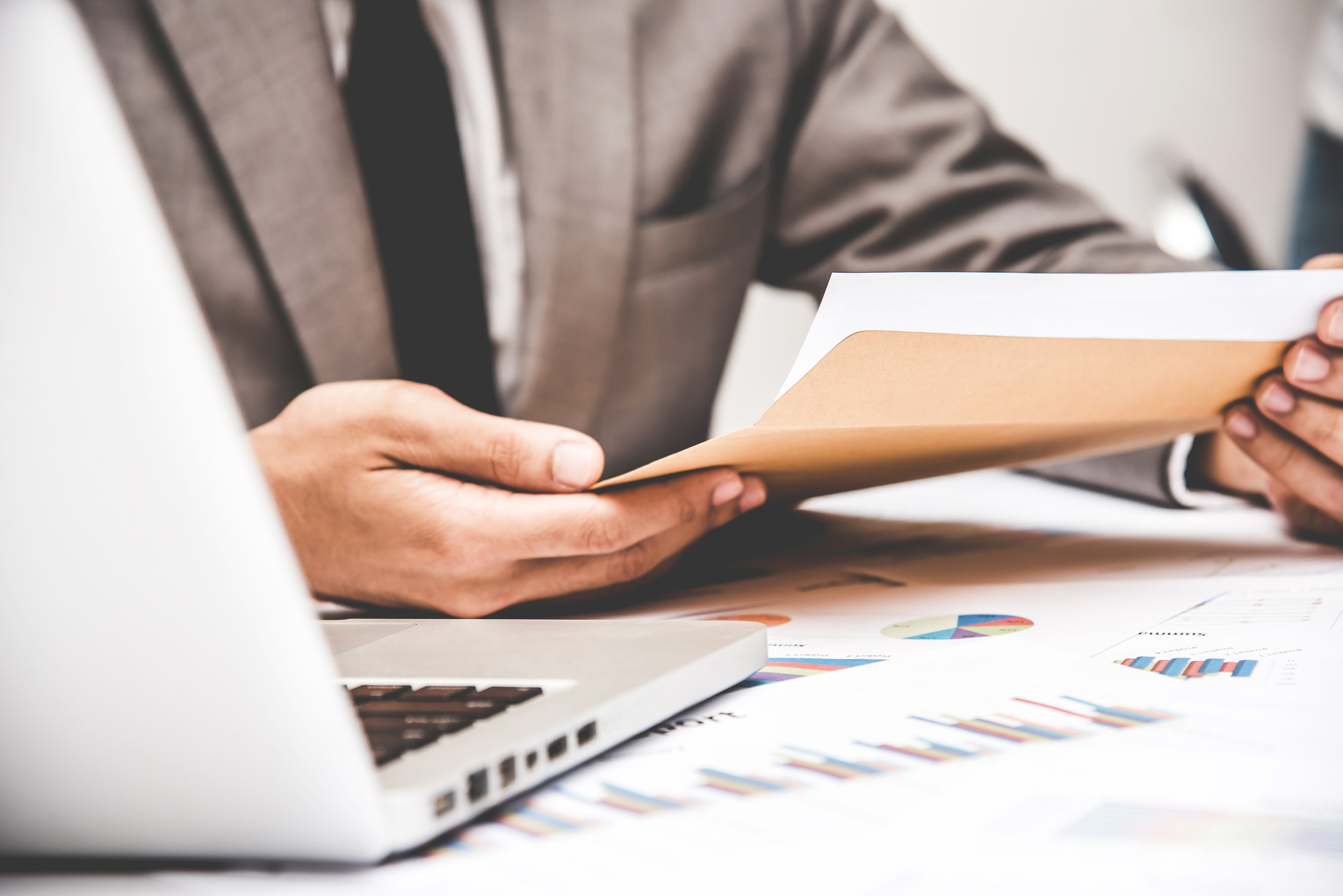 Businessman pulling out business document from brown envelope.