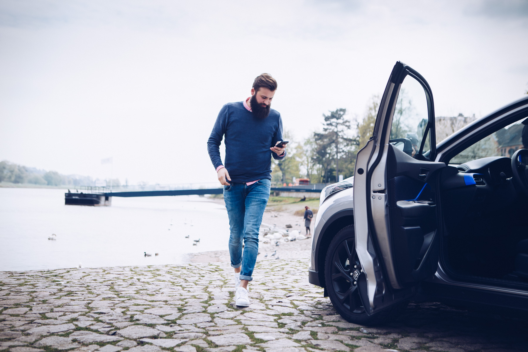 ©TomWoollard_Toyota_C-HR_car-editorial-lifestyle-man-with-beard-at-Dresden-river-looking-at-phone.jpg