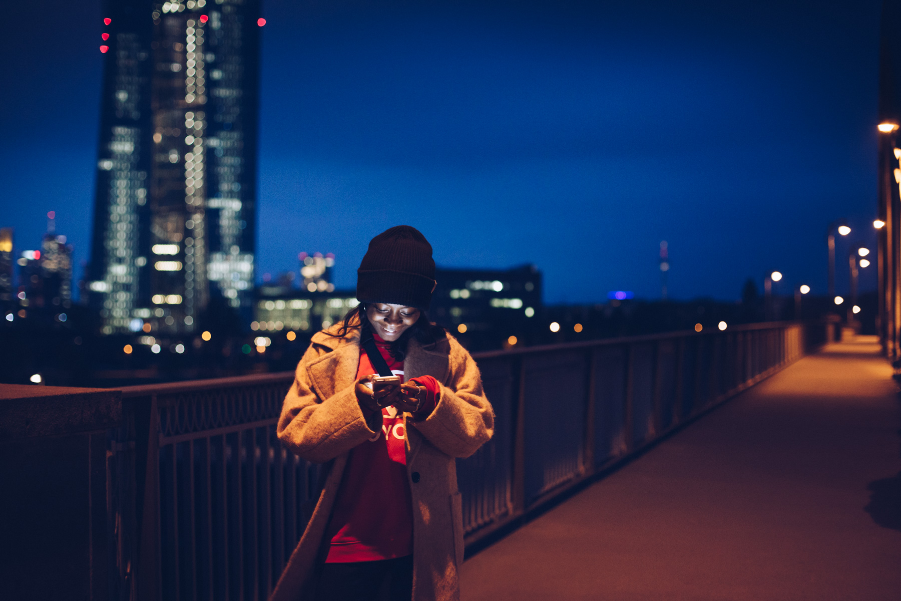 ©TomWoollard_lifestyle-editorial-young-woman-smiling-at-phone-message-nighttime-Frankfurt-skyline.jpg
