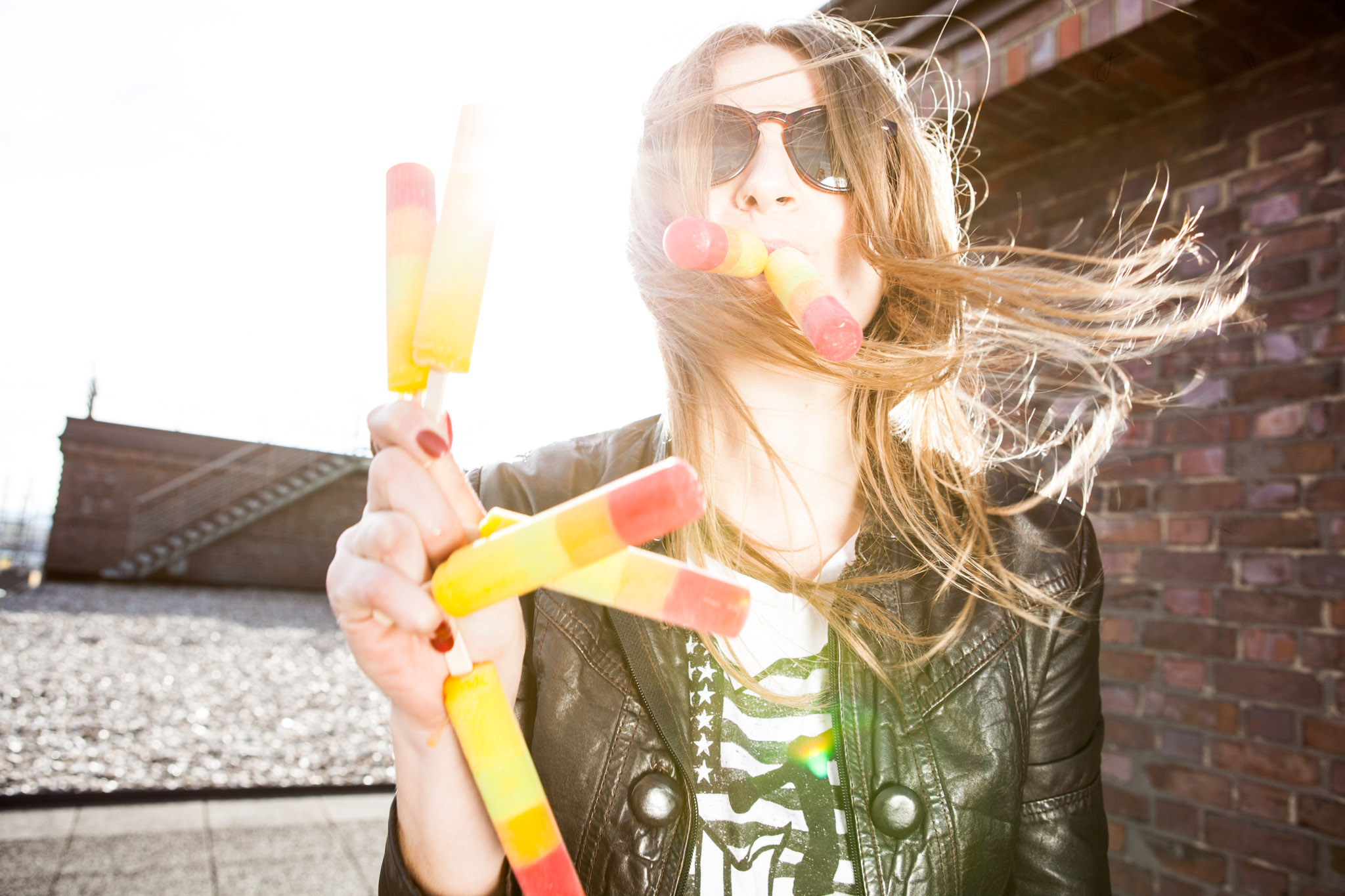 ©TomWoollard_editorial-lifestyle-young-stylish-woman-sunglasses-eating-ice-lolly-sunny-day-wind-hair.jpg