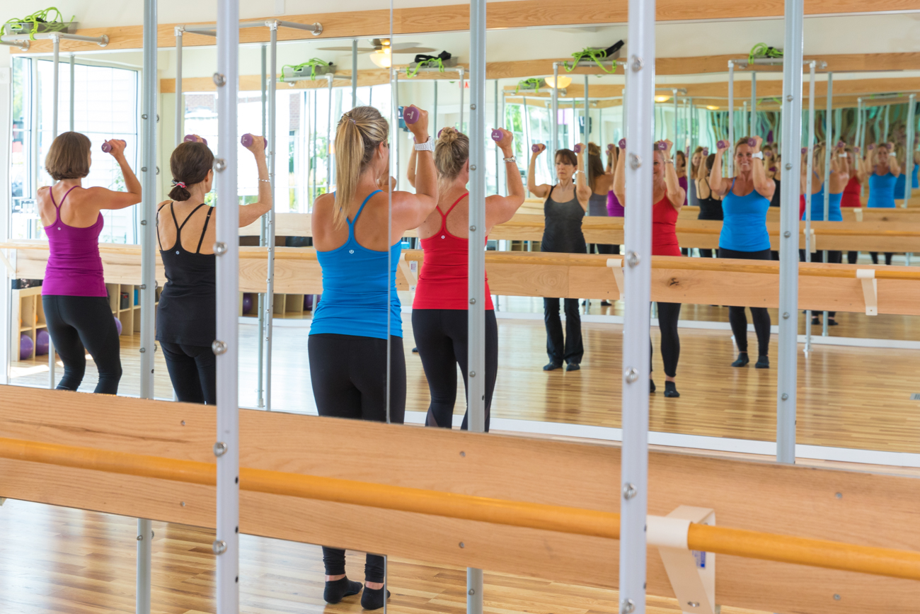 Invigorating - Our Barre classes will take you through a dynamic and invigorating workout from start to finish. Students are taught to focus on form and precision while performing small isometric movements in this music driven class which begins with a marching warm up. A sequence of upper-body exercises include free weights, push-ups, planks, etc. to target the biceps, triceps, chest, and back muscles. The Barre or Tower is used as a prop to balance while doing exercises that focus on isometric strength training (holding your body still while you contract a specific set of muscles) combined with high reps of small range of motion movements.  Barre classes use a combination of postures inspired by ballet, yoga and Pilates. The Barre or Tower is used as a prop to balance while doing exercises that focus on isometric strength training (holding your body still while you contract a specific set of muscles) combined with high reps of small range of motion movements.   What makes us different is that we can work on the Ballet Barres or Towers with an array of interesting props and our teachers come from all different backgrounds with diverse barre experience and impressive credentials. We have comprehensively trained teachers in  Barre, Pilates, and TRX.