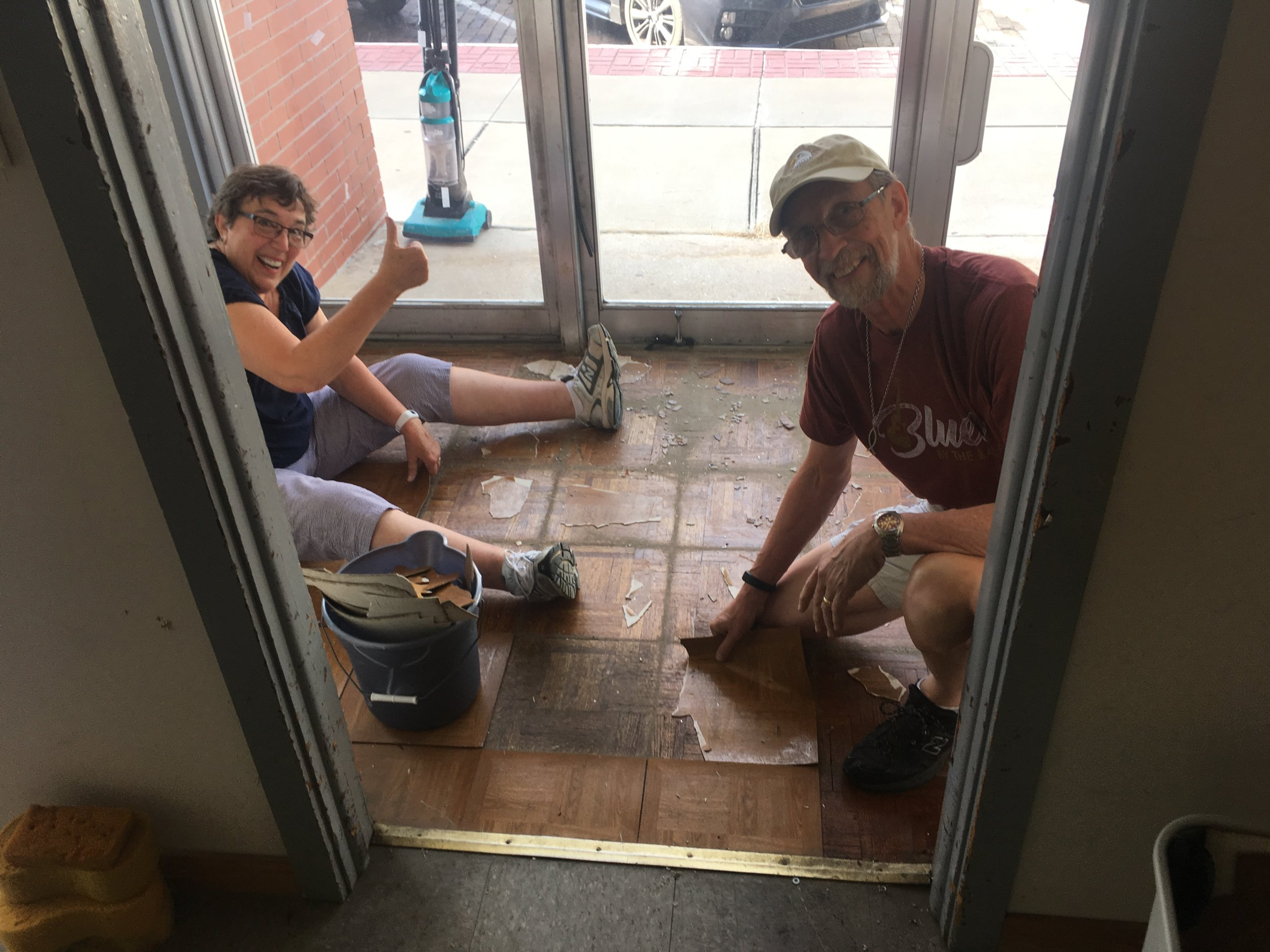 Hardworking volunteers helping remove fake linoleum parquet covering the real-wood parquet floor in the entry way.