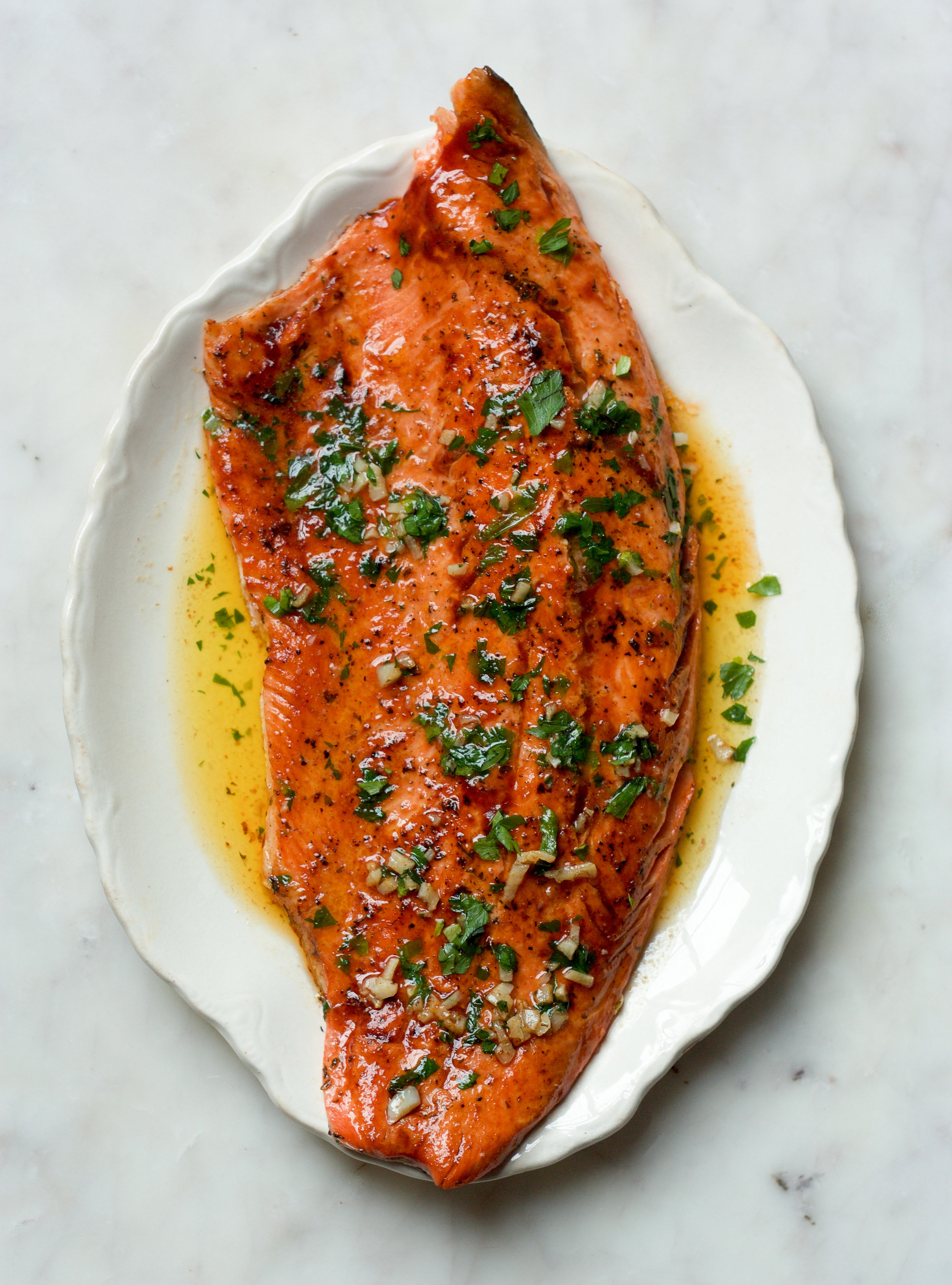 "Ingredients:   1 side of steelhead trout (roughly 2lbs)  4 cloves fresh garlic, diced  3 tbsp salted butter  1 tbsp Korean G ochujang paste   2 tbsp honey  1/2 cup chopped parsley  Method:  In a small bowl, add kochujang, honey and parsley, stir to combine and set aside.  Heat a 12"" non-stick skillet to medium-high. Add butter and garlic and cook for 1 minute until melted and just bubbling. Place trout in pan skin side down, making sure that every surface of flesh is touching the pan. Cook for 3-5 minutes and flip.  While the skin side is cooking (3 minutes), use a marinade brush to spread kochujang mixture evenly over the flesh side of the trout. Remove pan from heat and place trout under a moderate broiler for 5 minutes. (Alternatively, flip the fish over once more and cook for 1-2 minutes just until the marinade caramelizes slightly). Place on a serving dish along with any pan juices.   Serves 4"